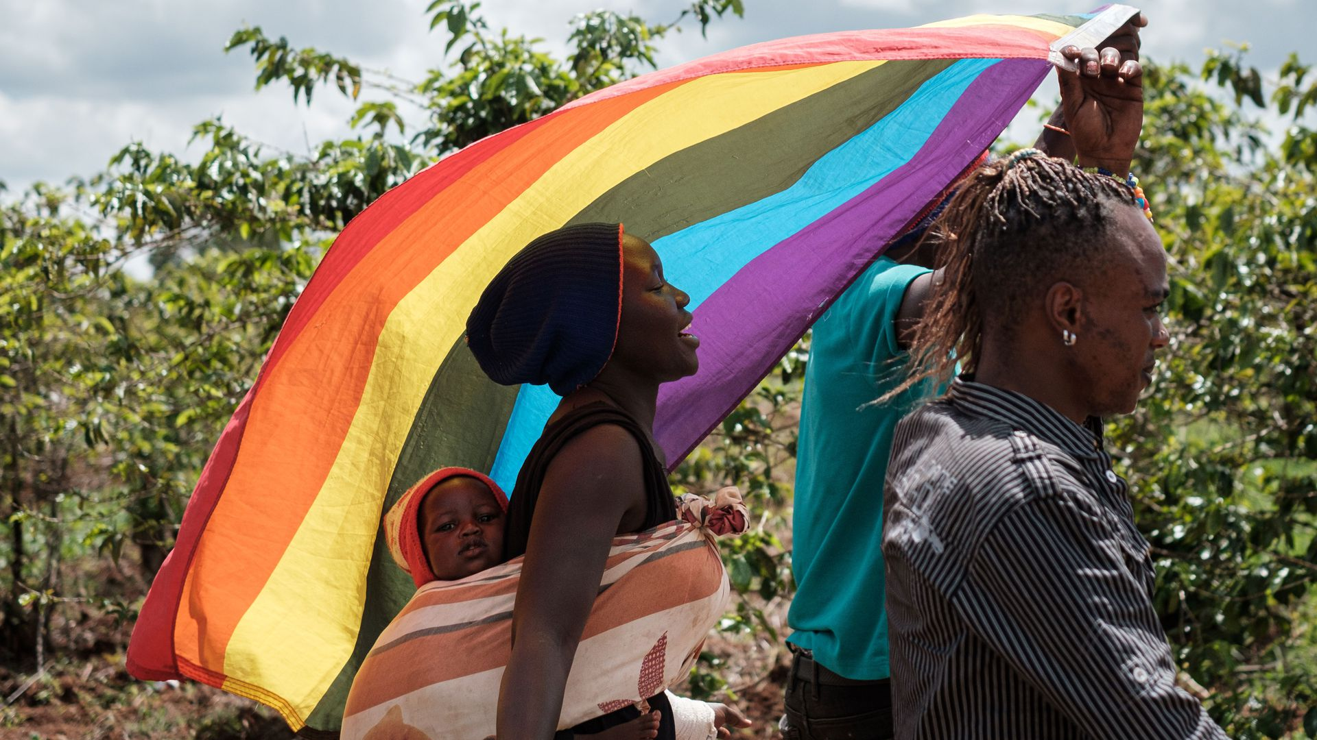 In this image, a man carries a rainbow flag while a woman carrying a baby in a papoose follows behind him.
