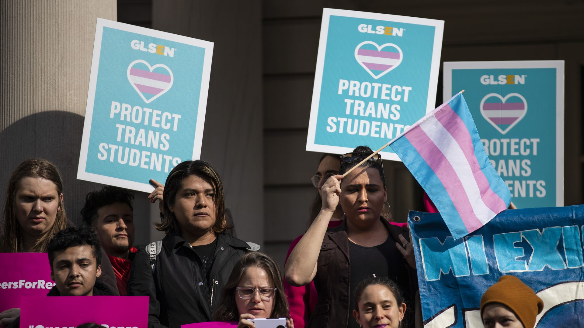 "In this image, a transgender pride flag is waved while others hold signs that read ""protect trans students"""