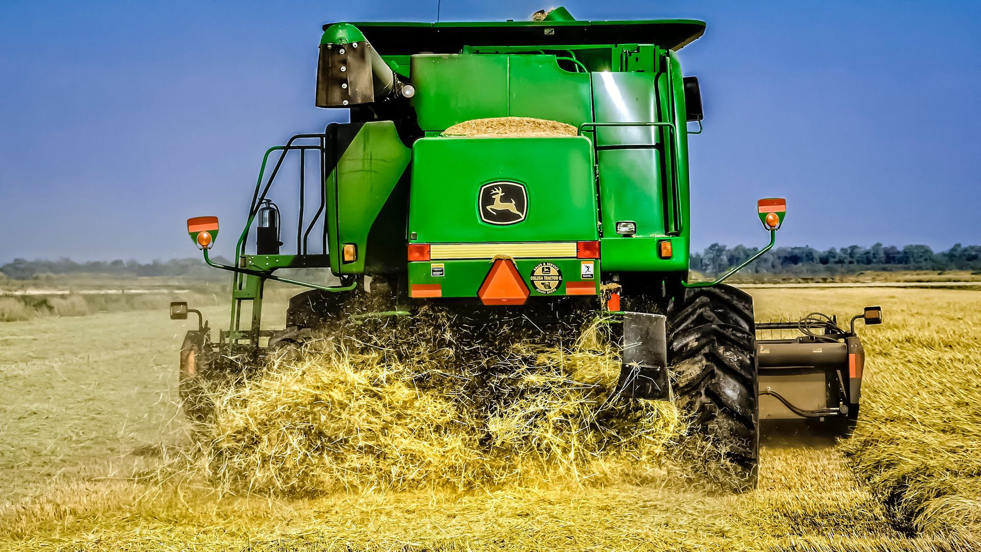 In this image, the back end of a John Deere tractor plows through a field.