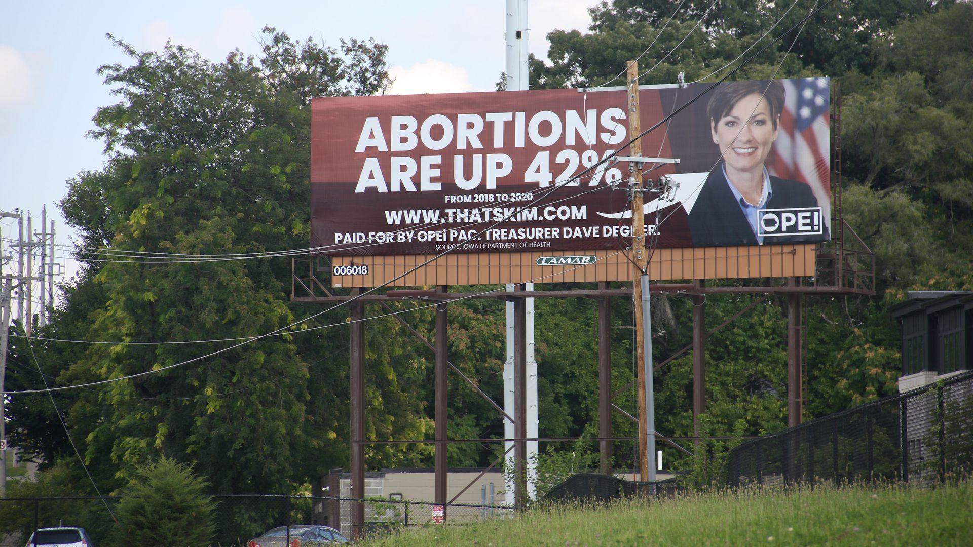 A billboard of Gov. Kim Reynolds alongside I-235 East.