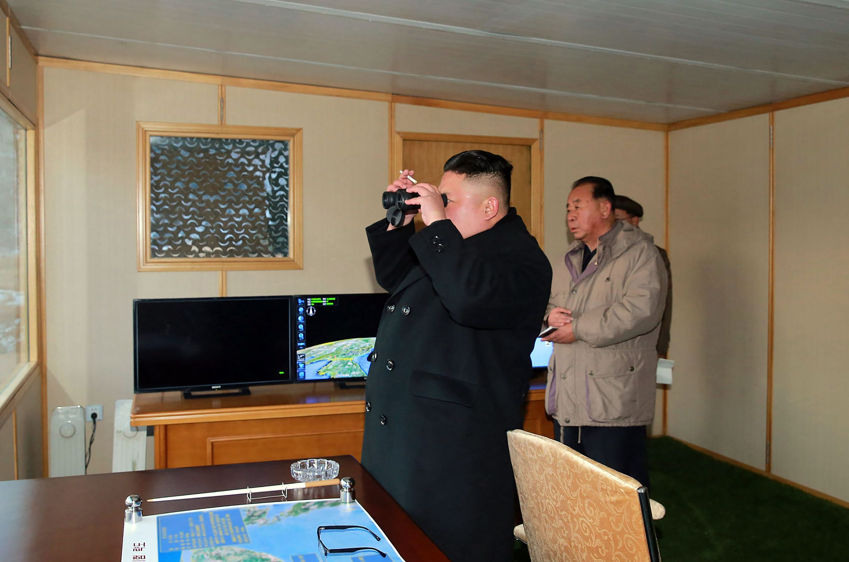 Kim Jong-un looks through binoculars.