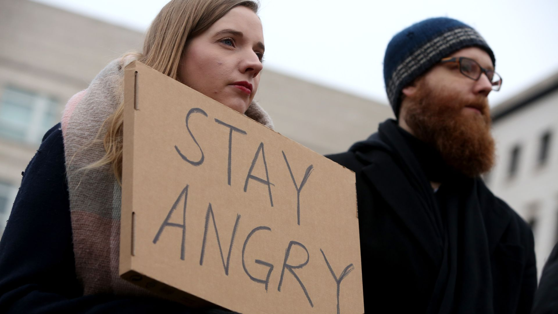 "A young woman holds a sign that reads, ""Stay Angry."""