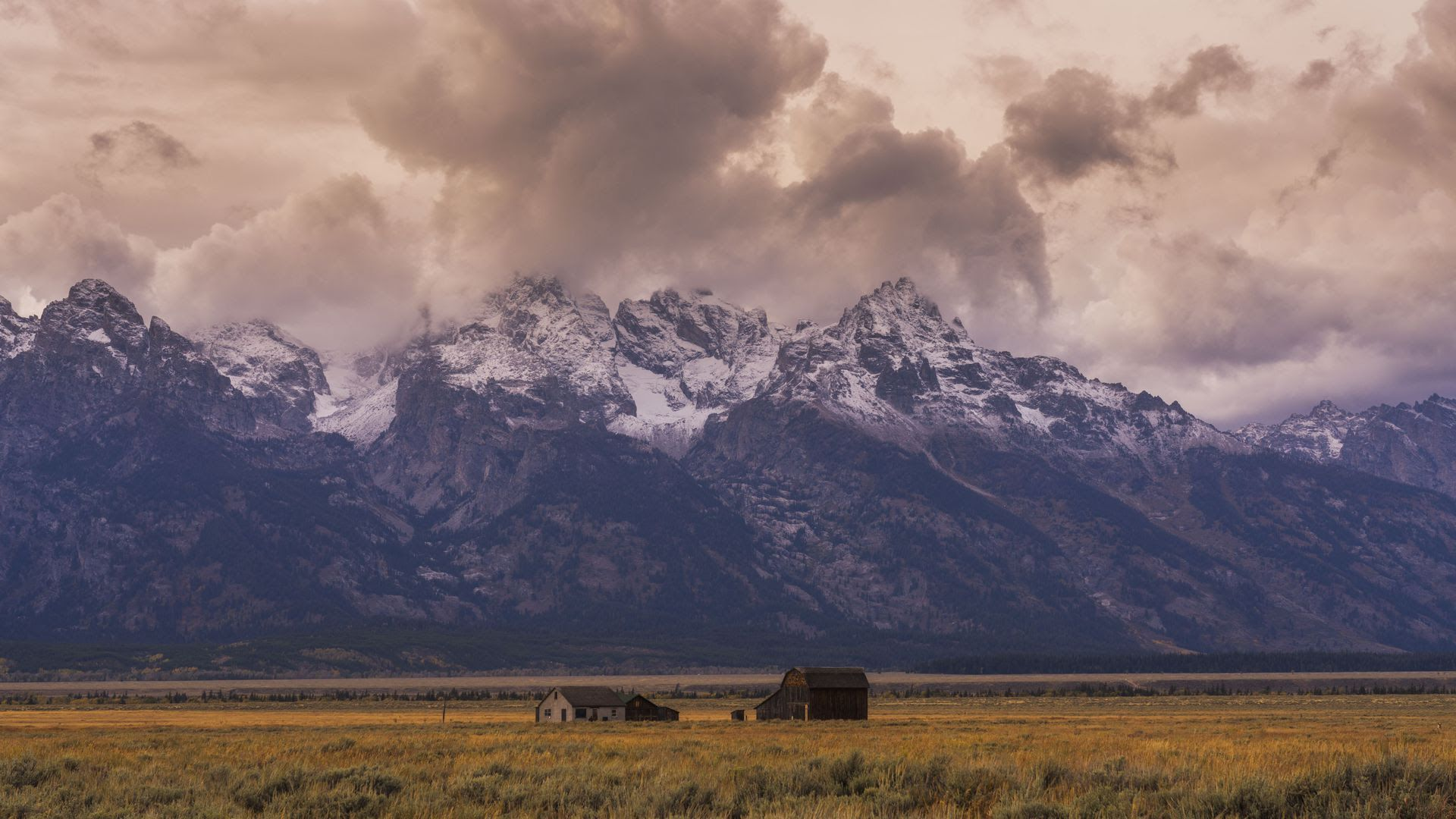 A cabin in front of a mountain range in Grand Teton National Park, Wyoming.