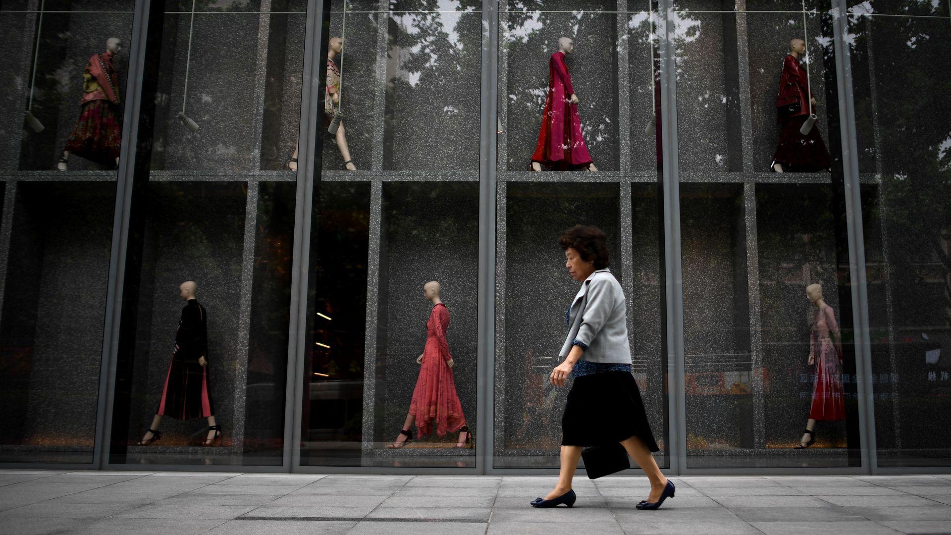 Chinese woman walking past mall