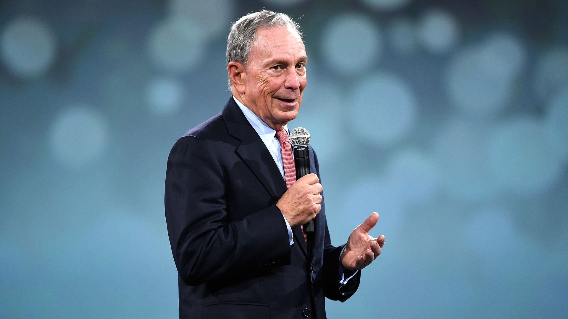 Mike Bloomberg smiles on stage