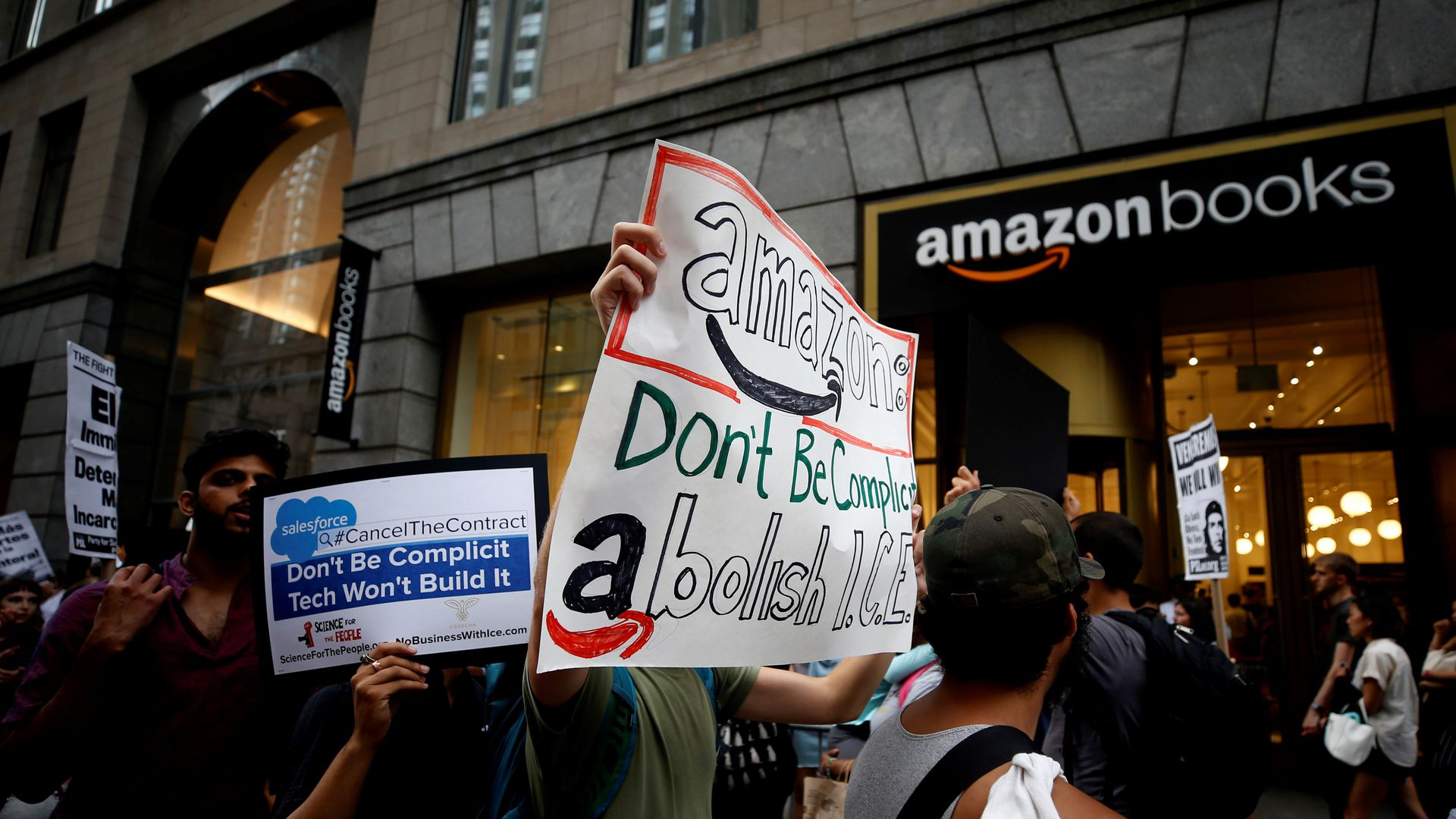 Protesters hold anti-ICE signs in front of an Amazon bookstore