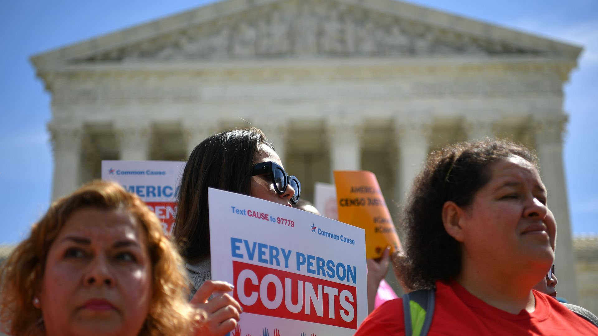 "Protesters wave signs that say ""Every person counts"" in front of the Supreme Court building"