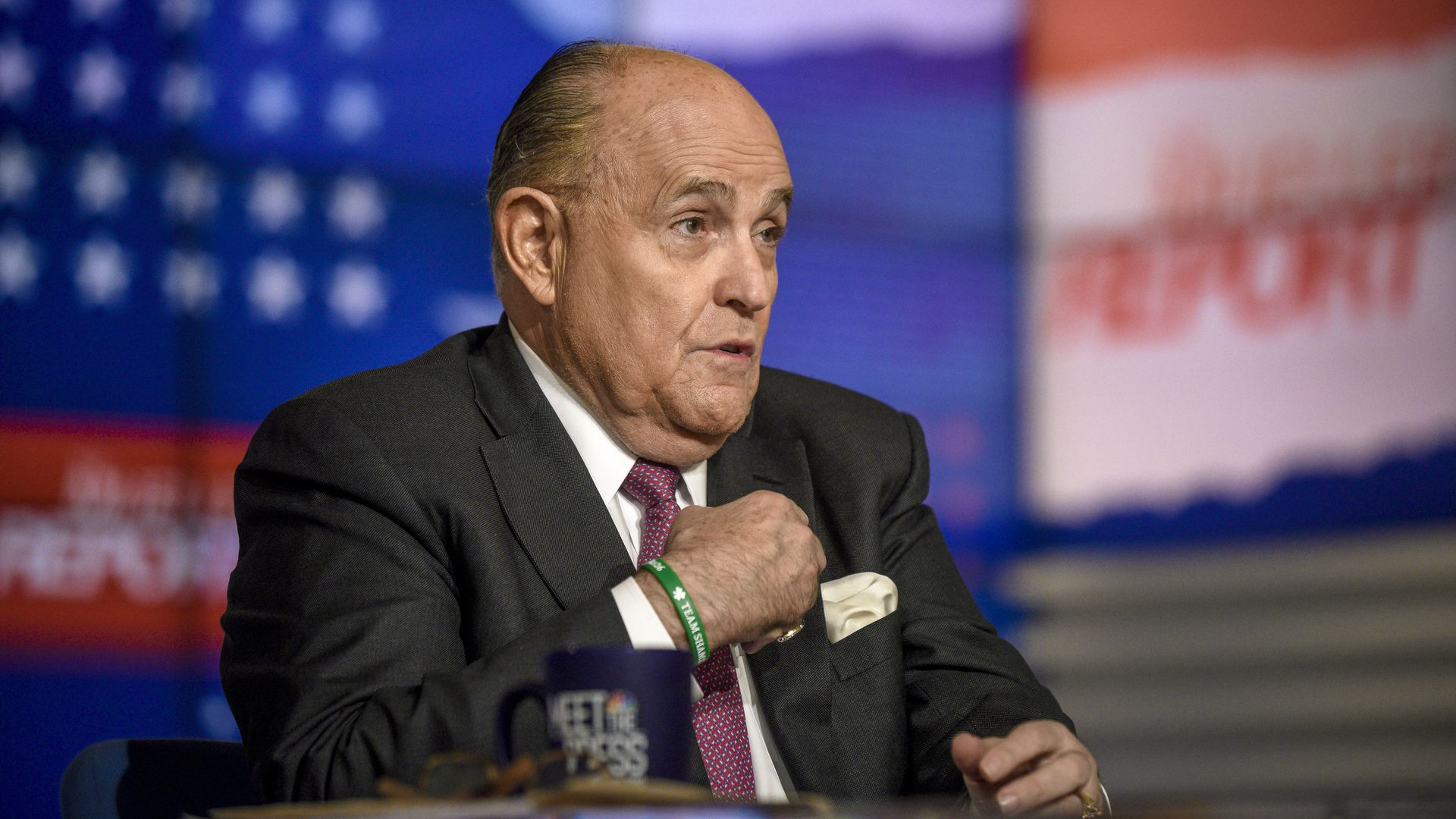 In this image, Rudy sits in a suit and tie and gestures to himself while sitting at a desk with the American flag in front of him.