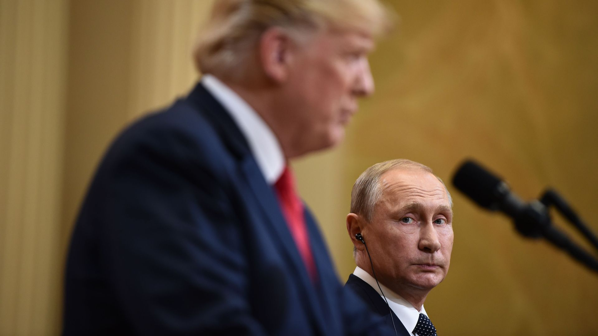 Vladimir Putin in background in focus looks concernedly at Trump, in foreground, blurry.