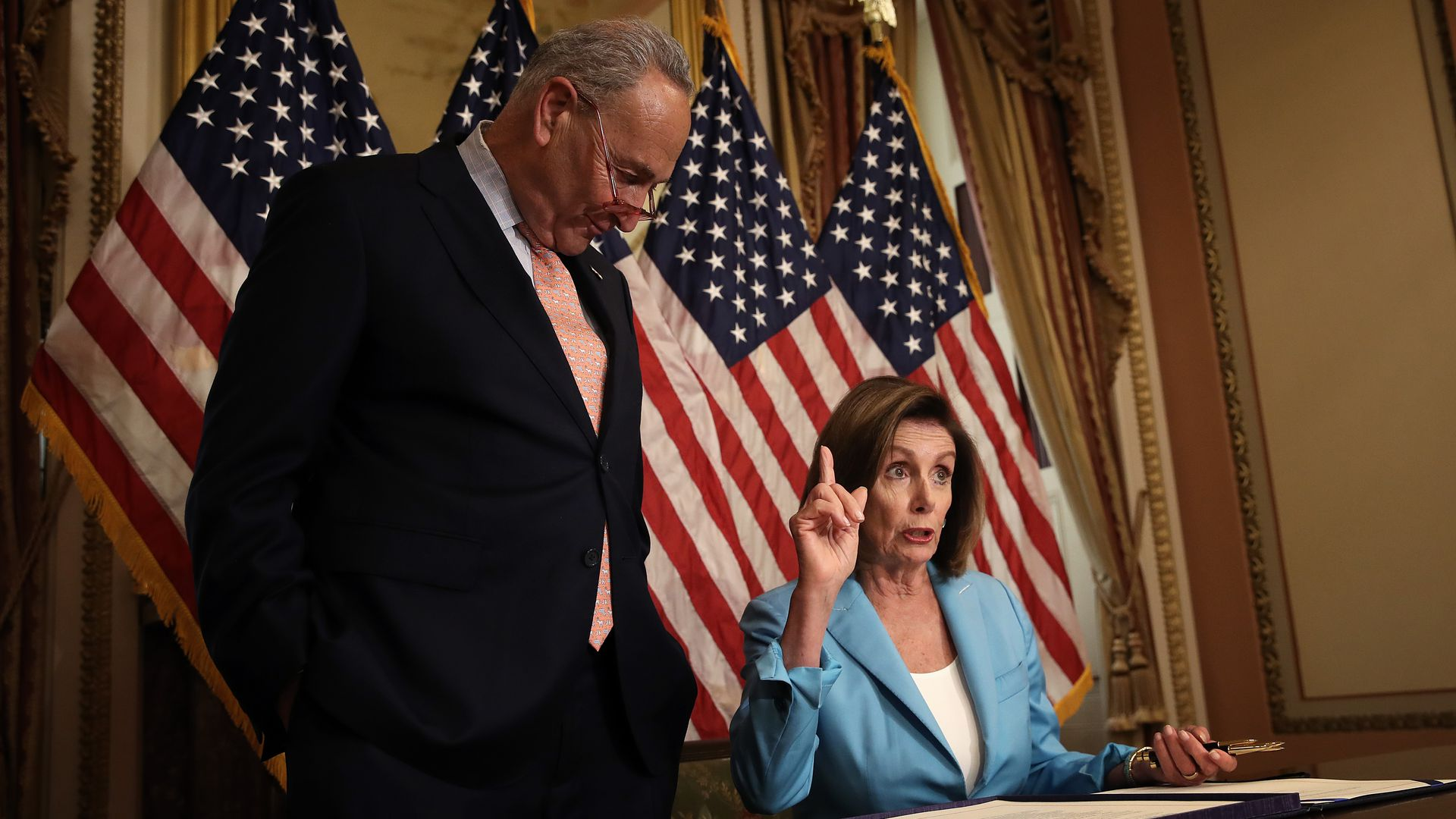 Senate Minority Leader Chuck Schumer (L) (D-NY) and Speaker of the House Nancy Pelosi (R) (D-CA) participate in a signing ceremony in Washington, DC.