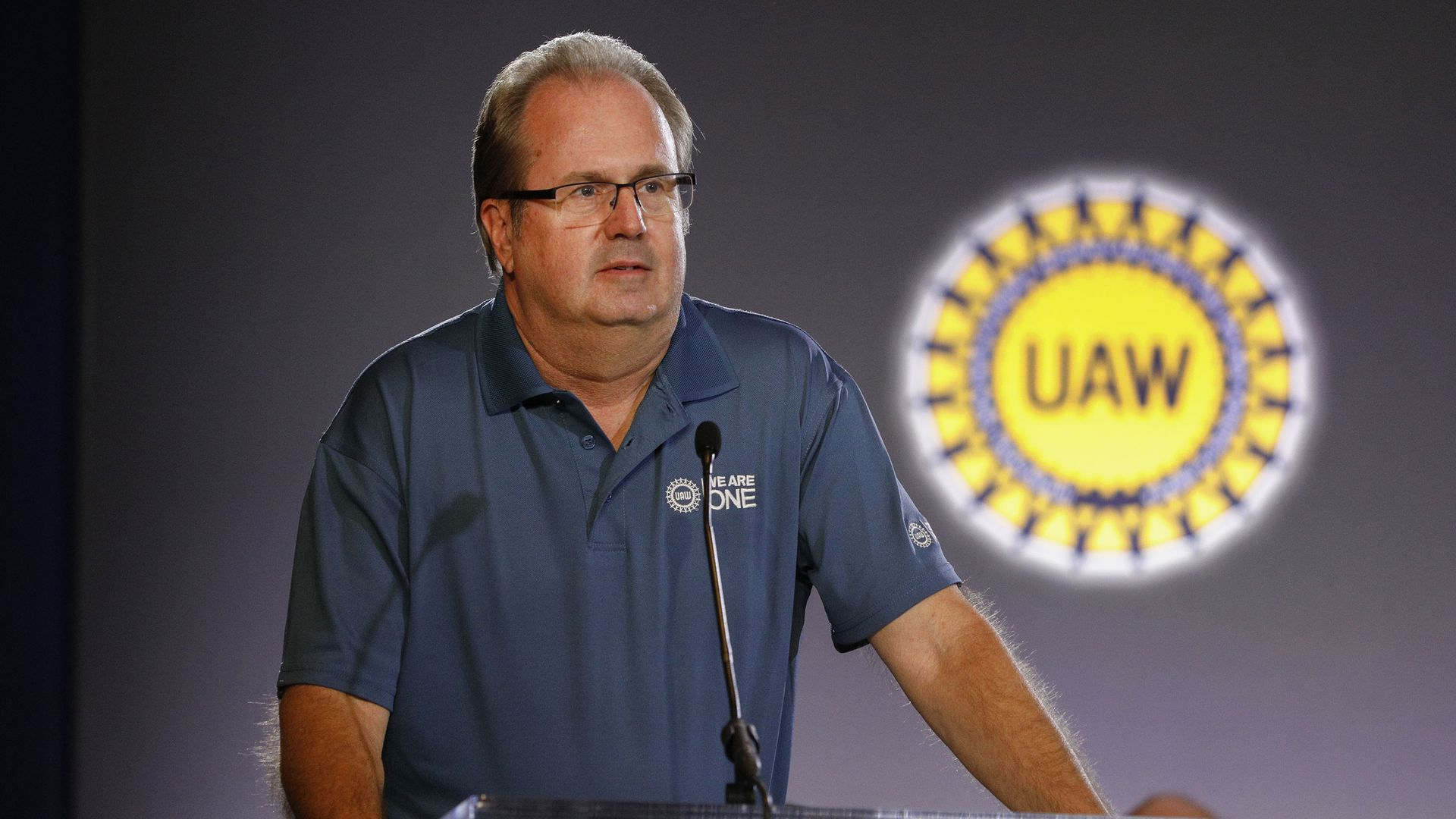 In this image, UAW president stands in front of a clear plastic podium.