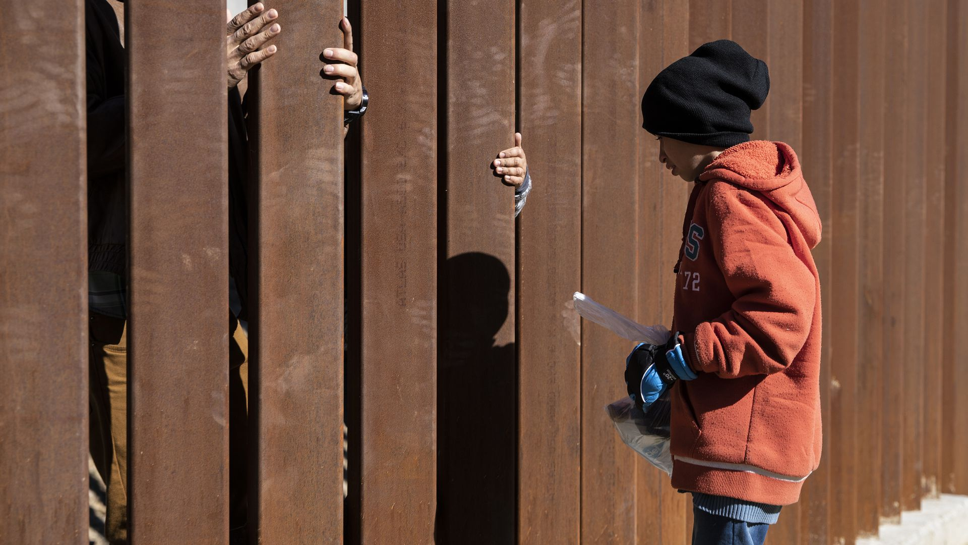 A young migrant boy with an orange hoodie and black hat stands on one side of the border wall.