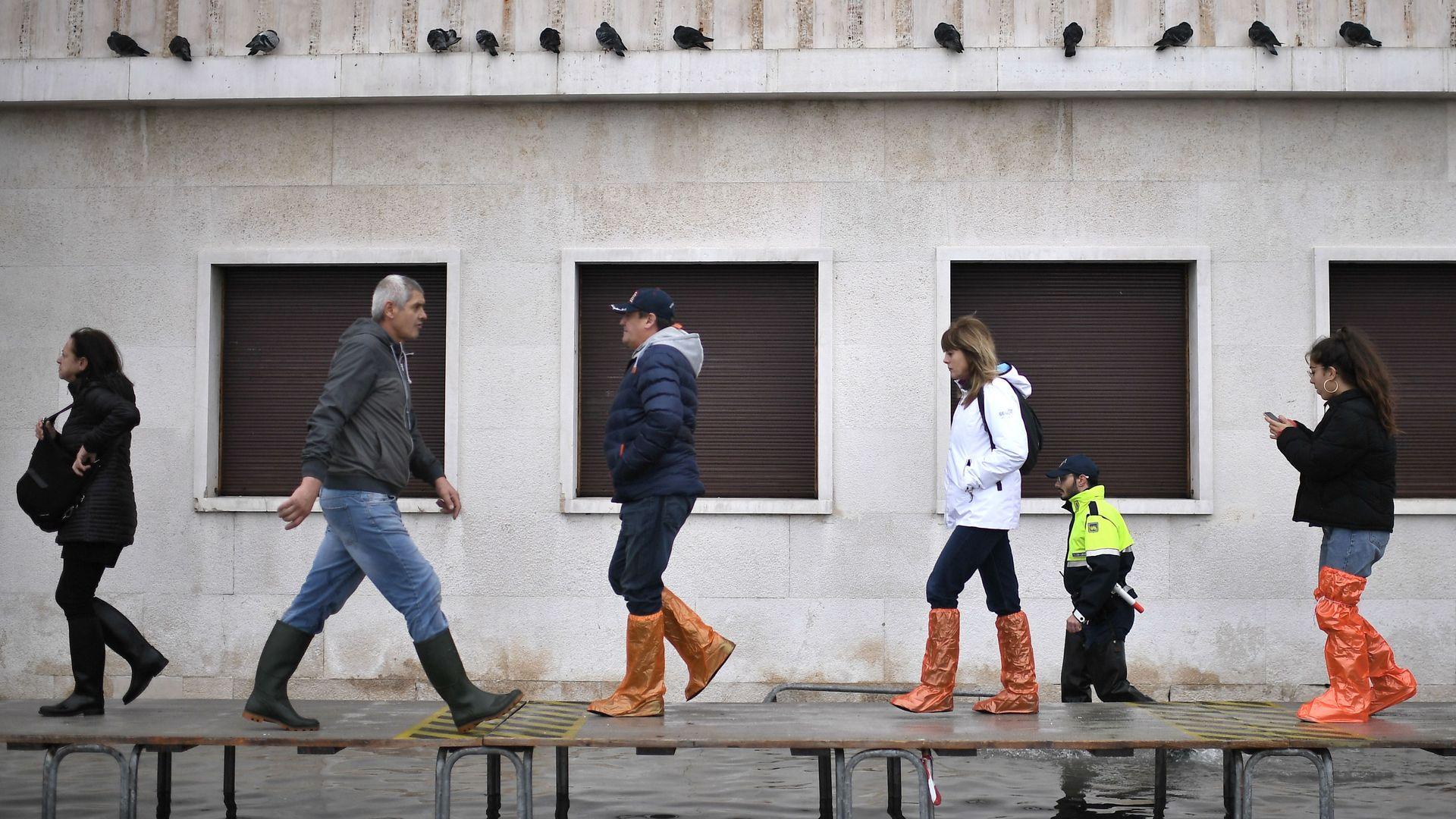 People walk on a footbridge across a flooded street in Venice.