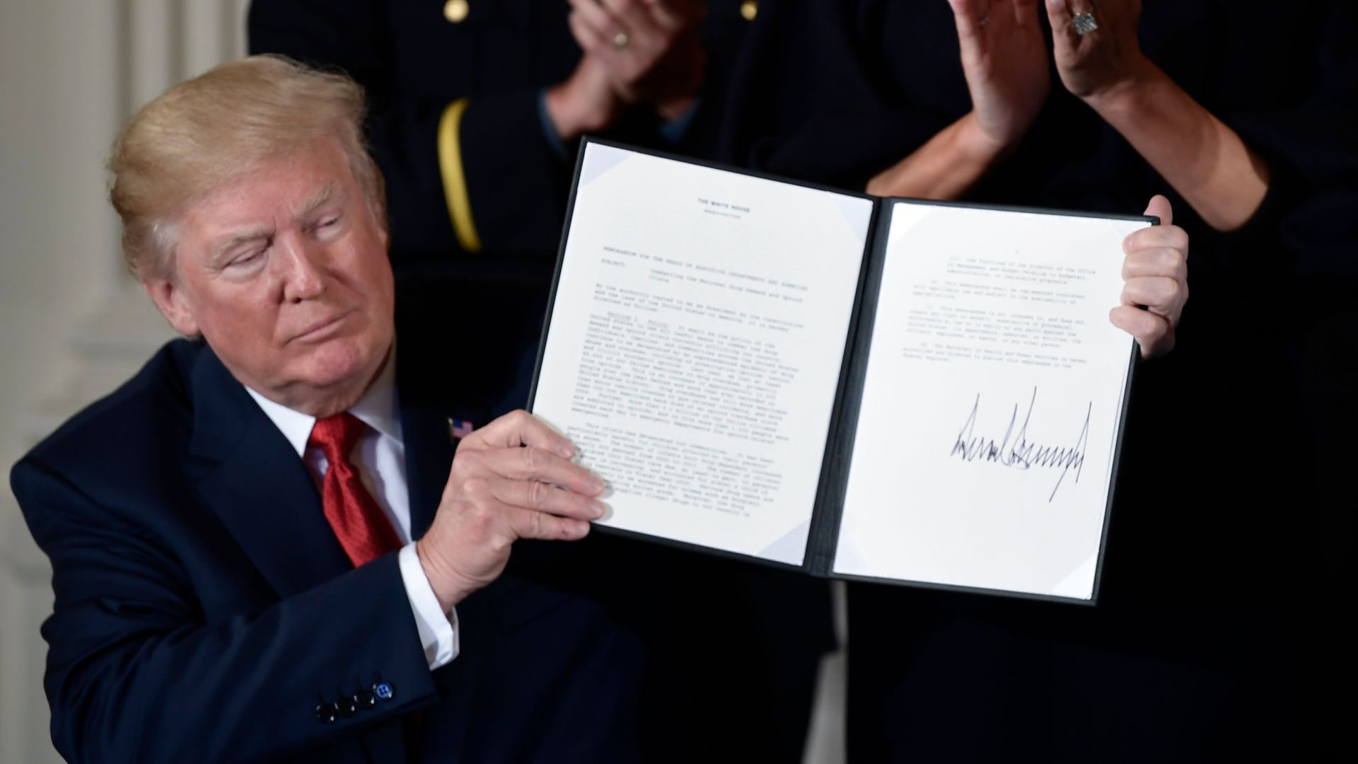 President Trump holding up a signed memo