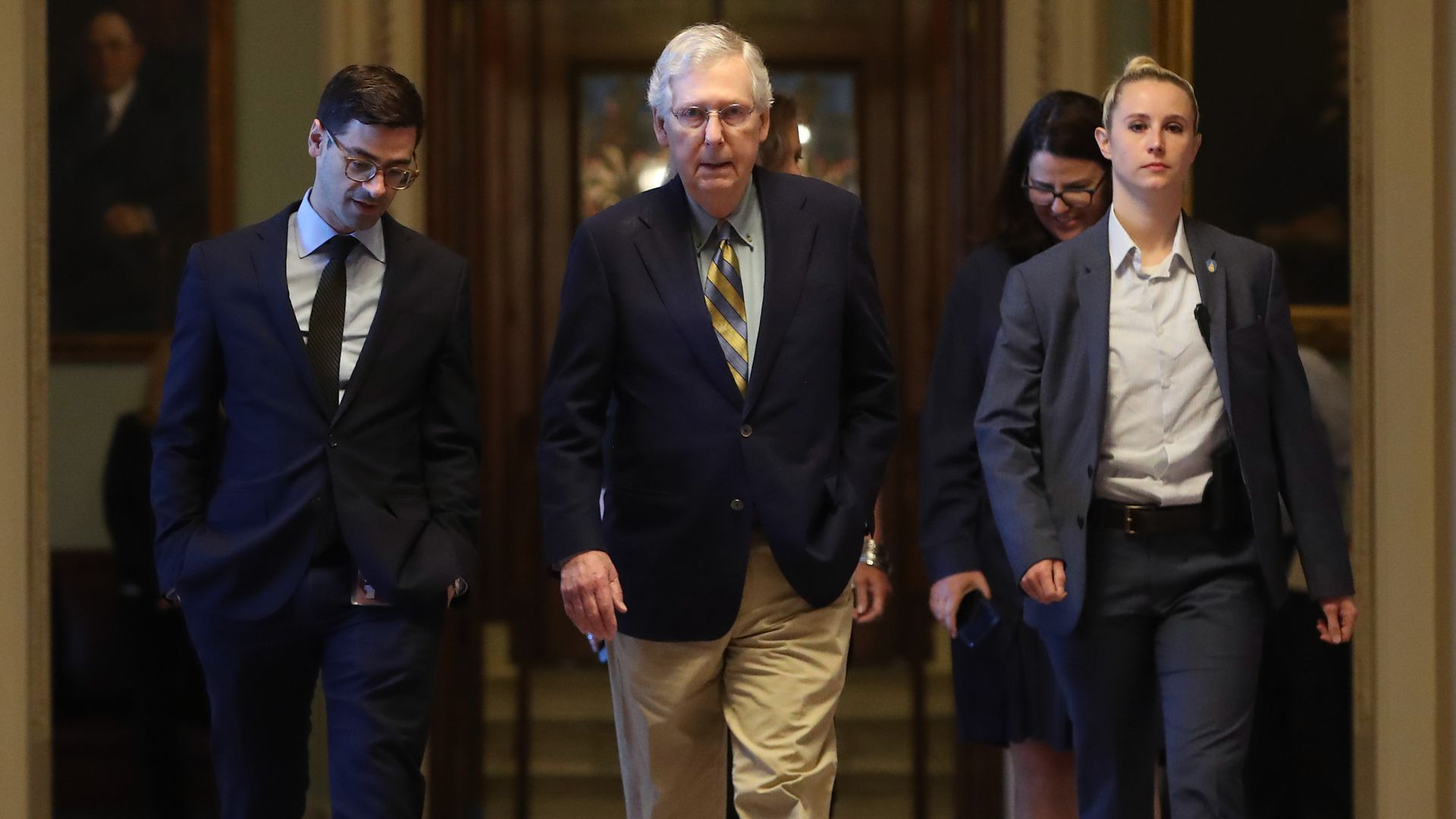 Senate Majority Leader Mitch McConnell of Kentucky walks through the Senate with two aides.