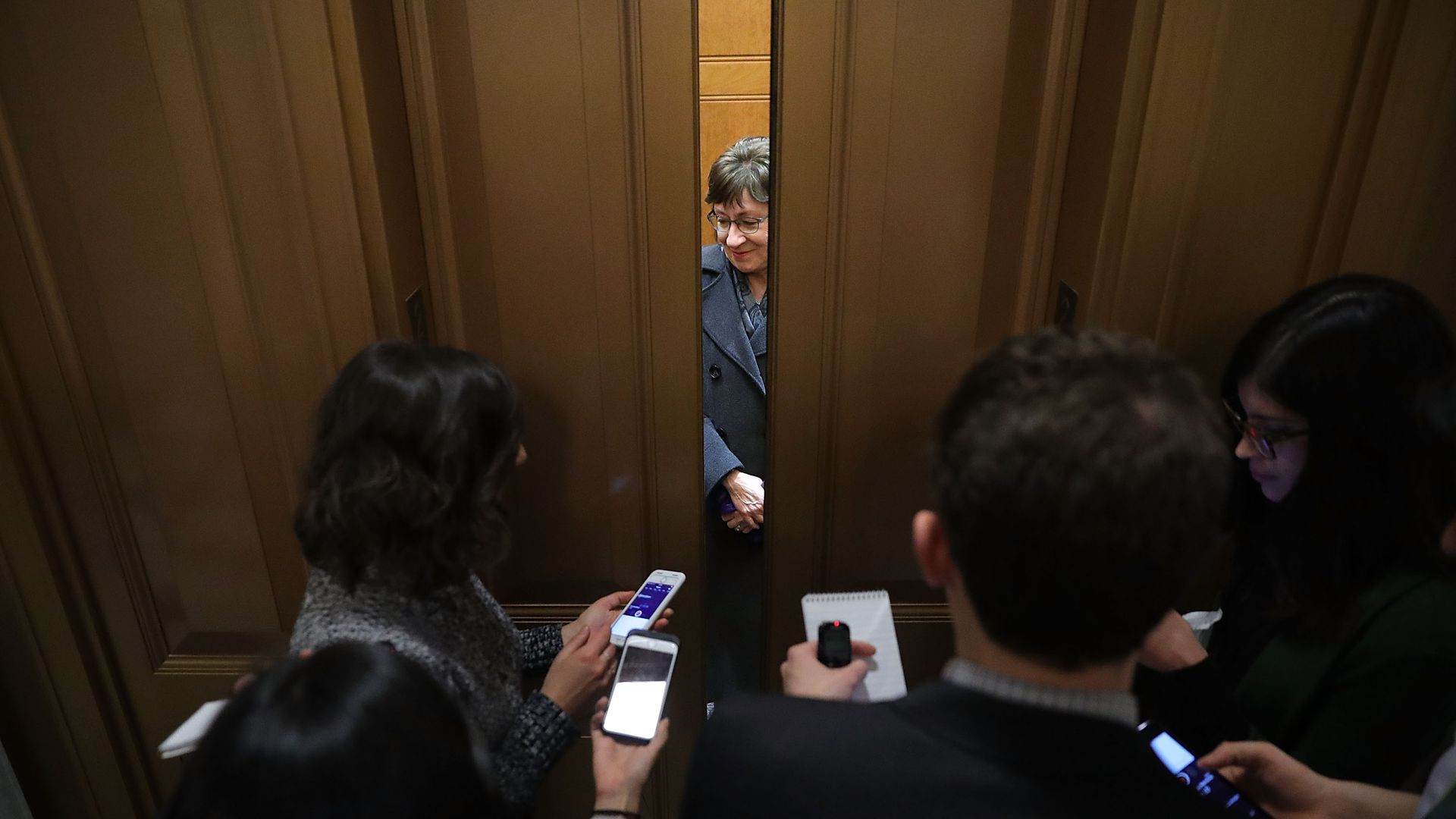 Susan Collins with elevator doors closing on her and reporters holding out recorders