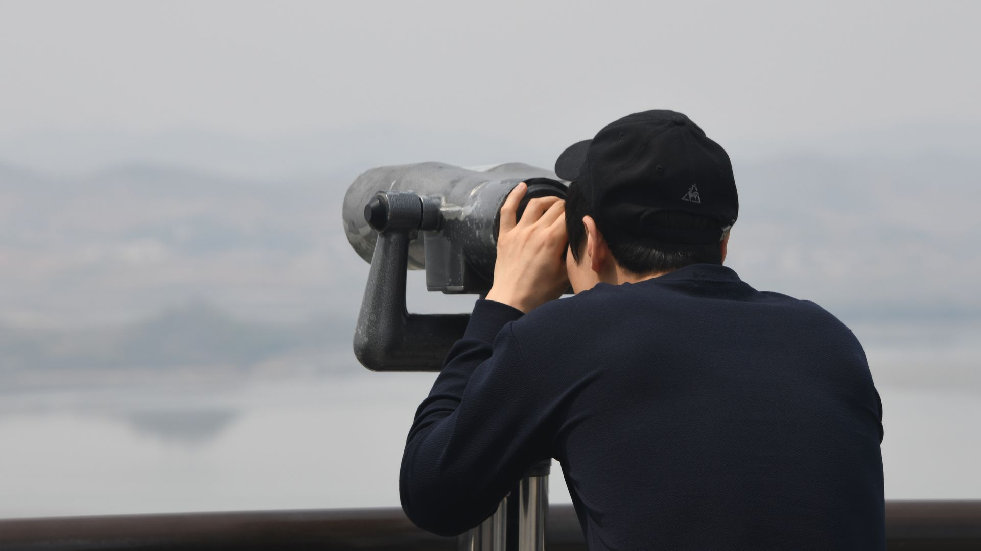 A visitor, wearing all black, looks towards North Korea through binoculars at a South Korean observatory, with a white sky.
