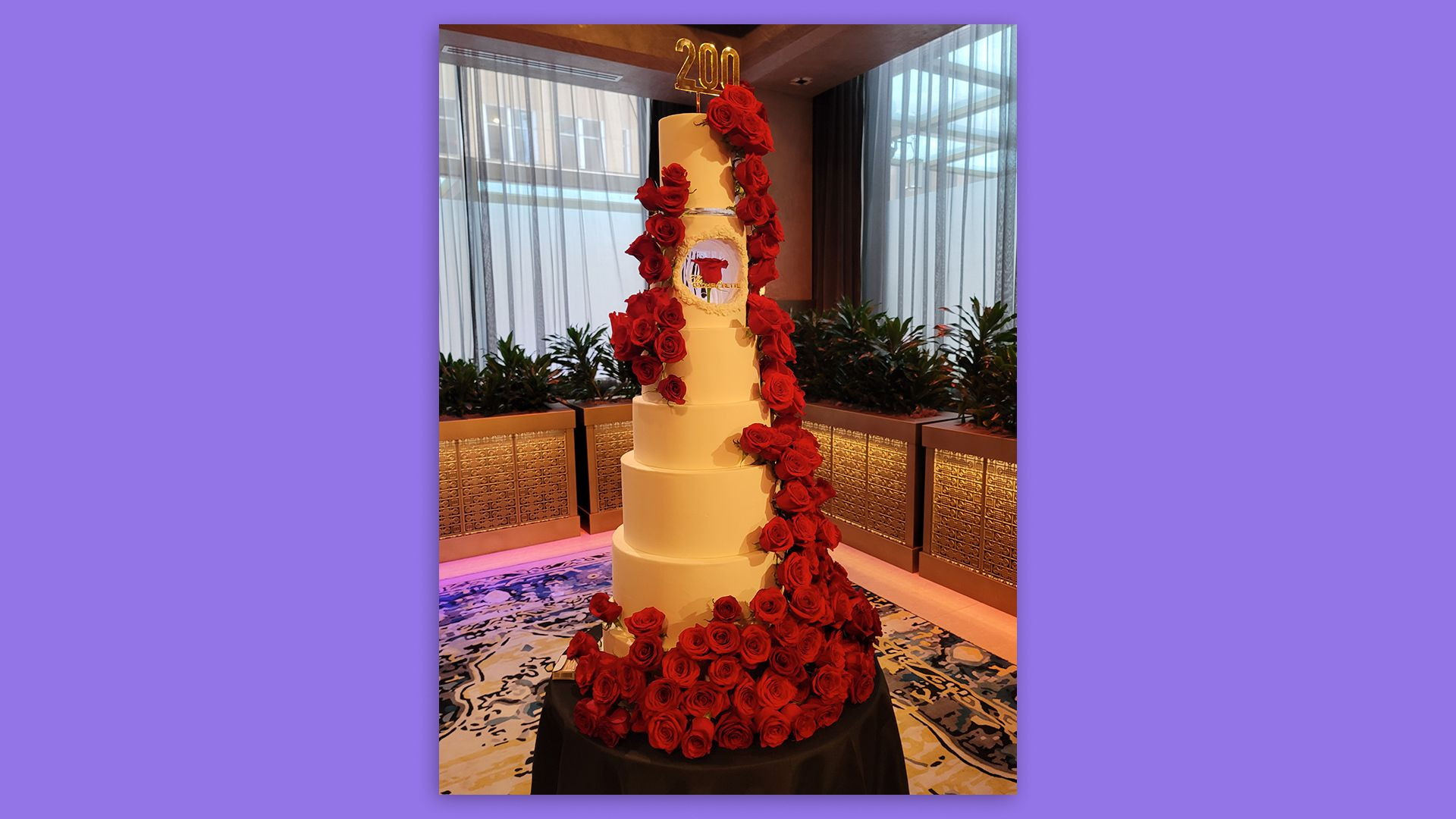 large tiered white cake covered in red roses