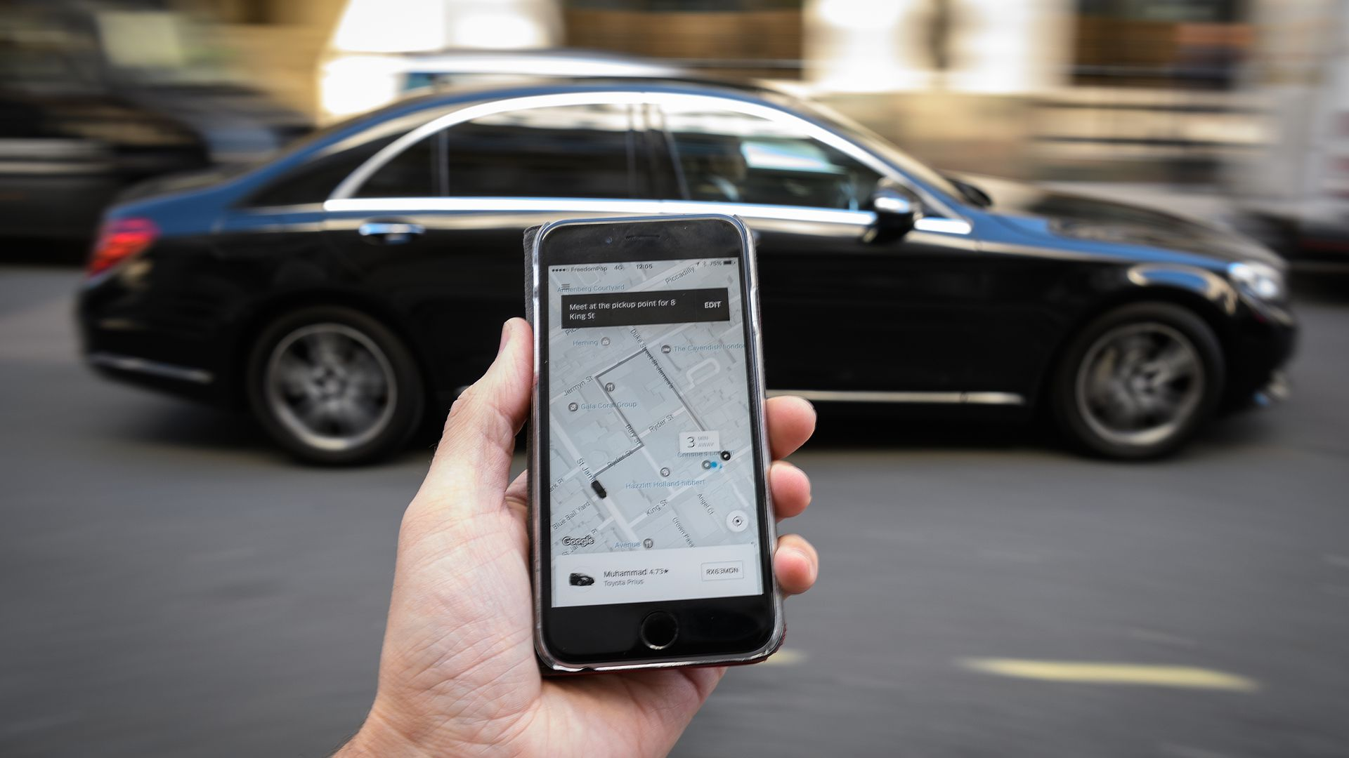 Outstretched hand holds phone with Uber app open