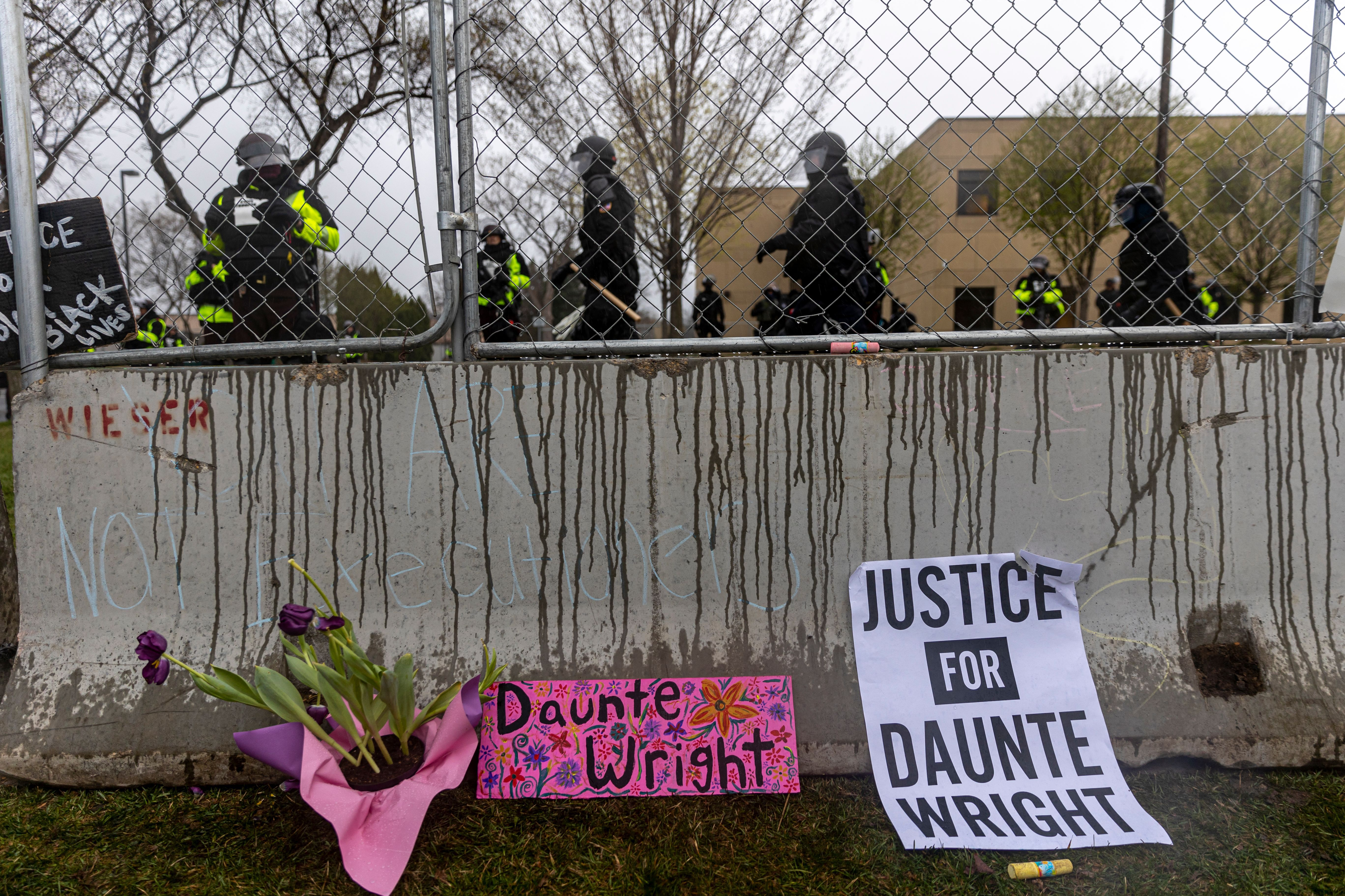 Flowers and signs are left in front of the security fence at the start of curfew to protest the death of Daunte Wright who was shot and killed by a police officer in Brooklyn Center, Minnesota