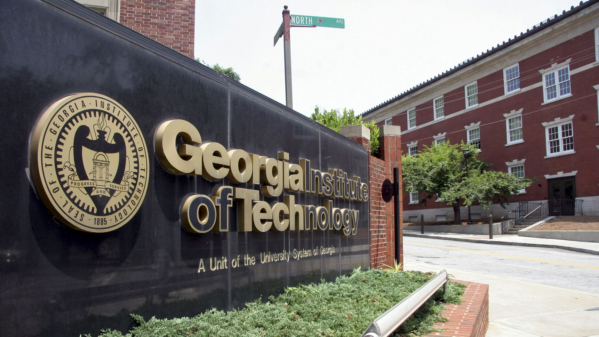 A black sign with gold lettering positioned at the entrance of the Georgia Tech campus.