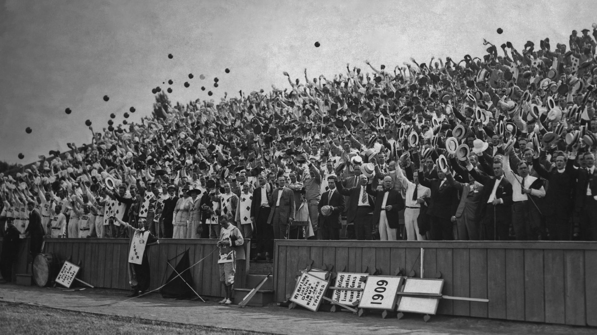 A black and white photo of college graduates throwing caps into the air