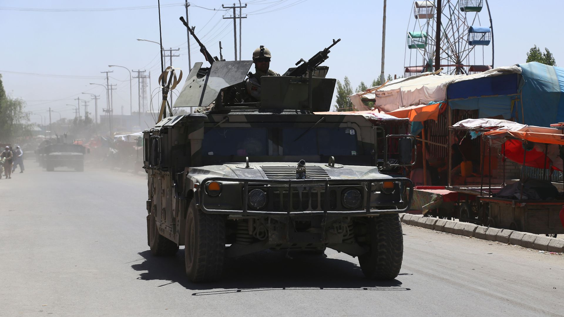 Afghan security forces drive in a tank.