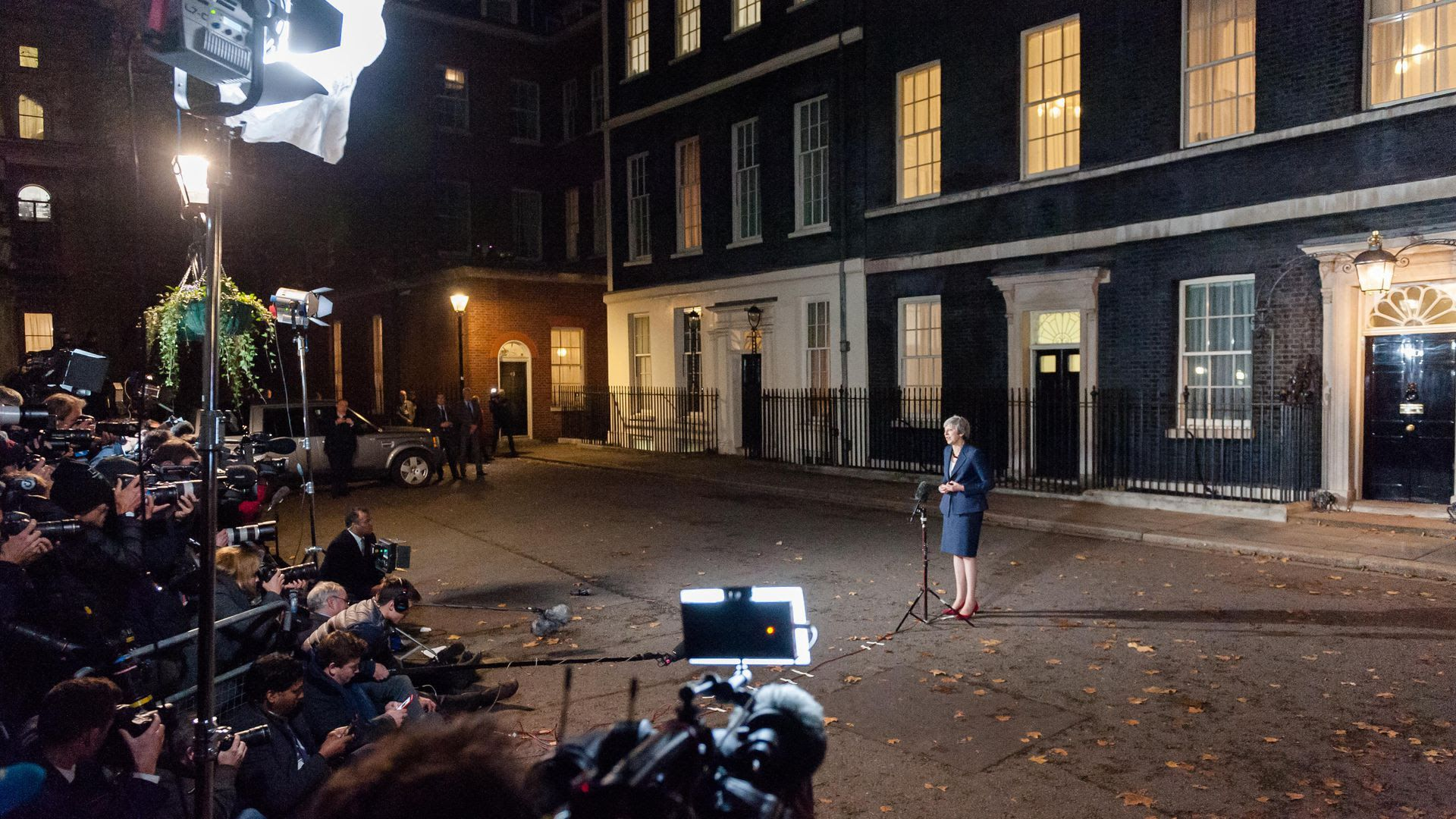 Theresa May stands before a swarm of media at nighttime.