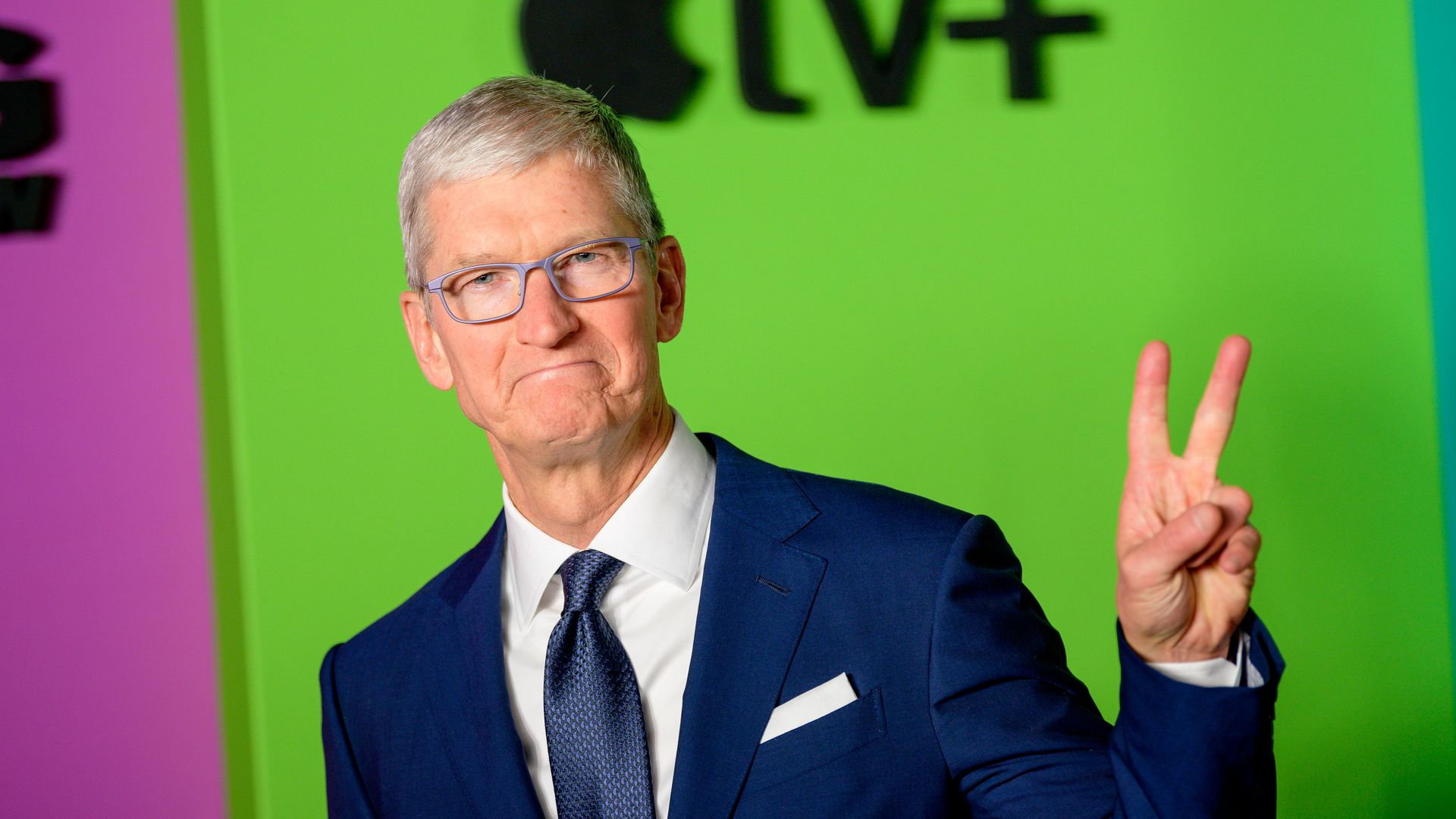 Tim Cook raising a few fingers, with an Apple logo in the background.