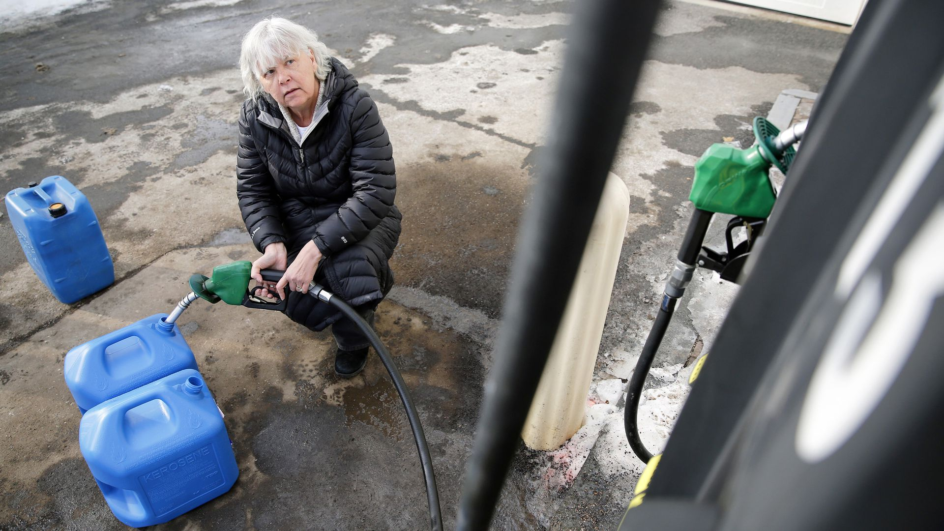 Lady with white hair crouches down filling three blue gasoline jugs with gasoline.