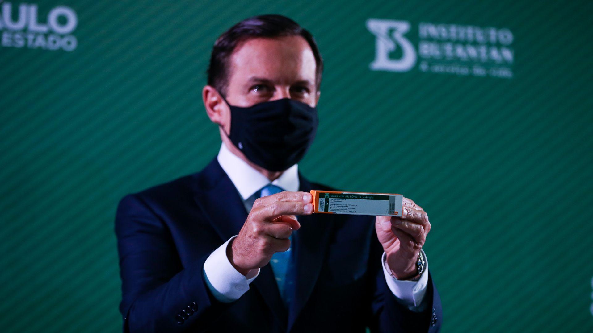 Foto do mascarado João Doria segurando uma caixa da vacina CoronaVac durante entrevista coletiva