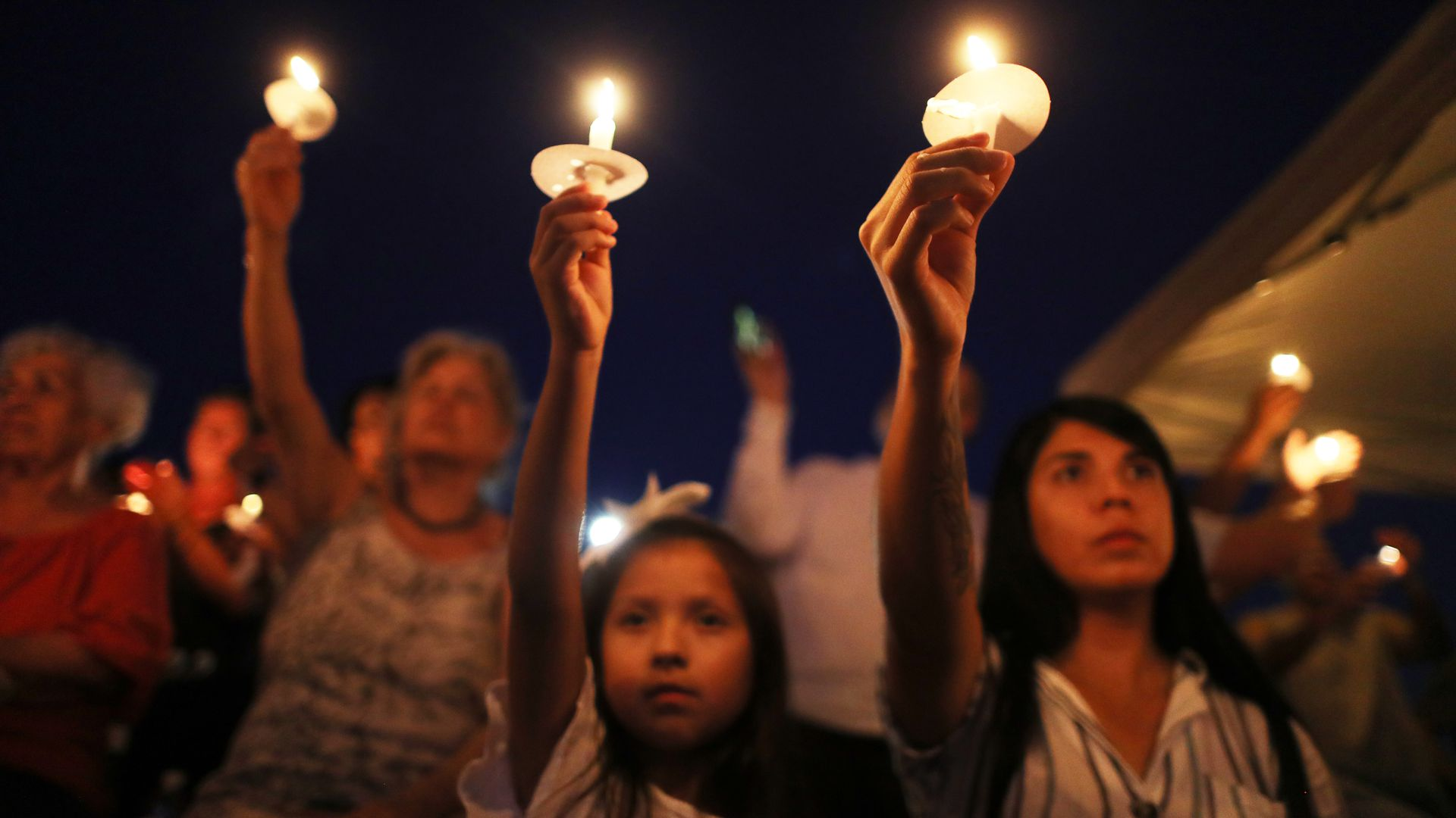 Mourners holding up candles at a vigil for those lost in El Paso.