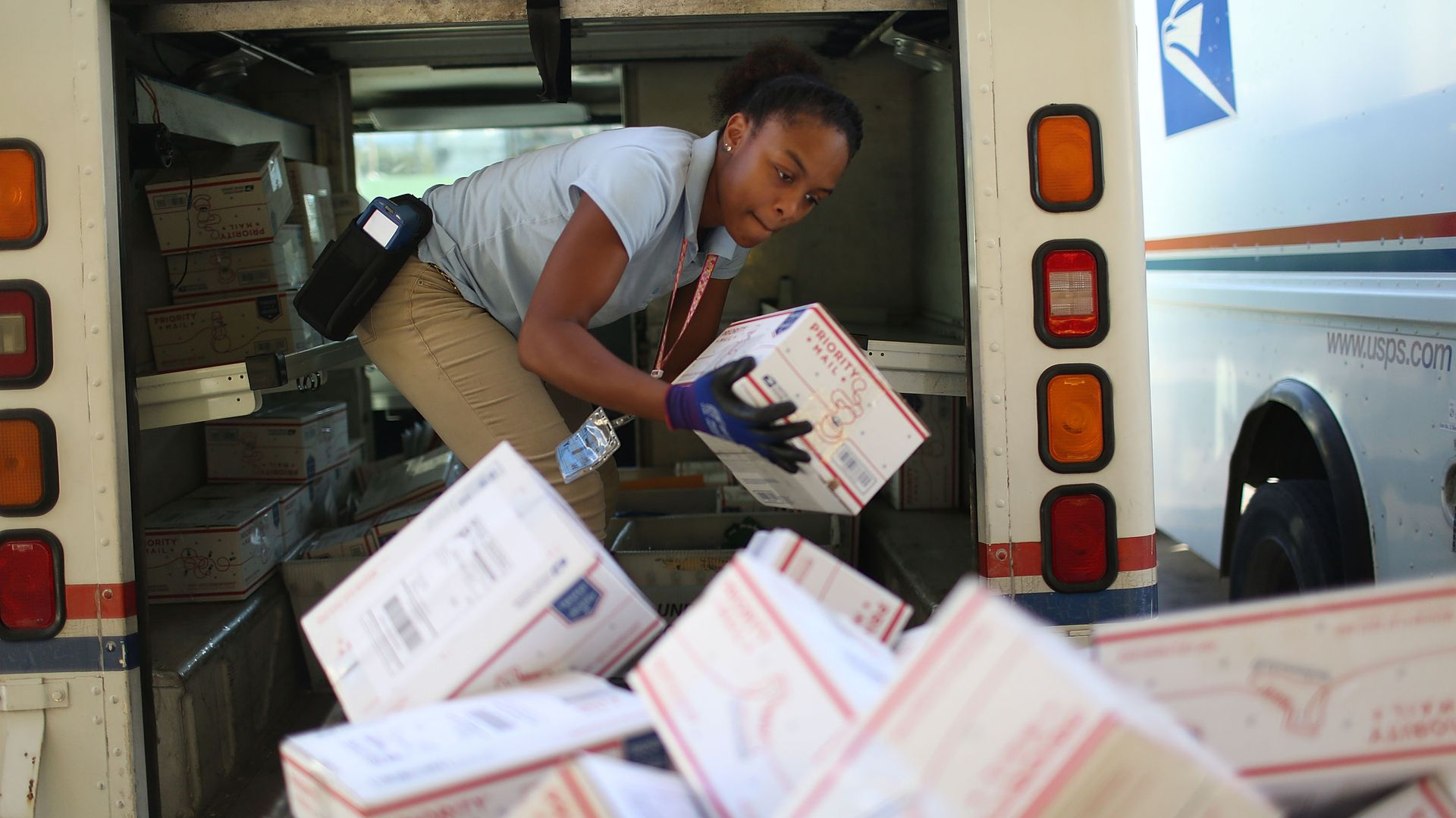 Postal employee unloading boxes
