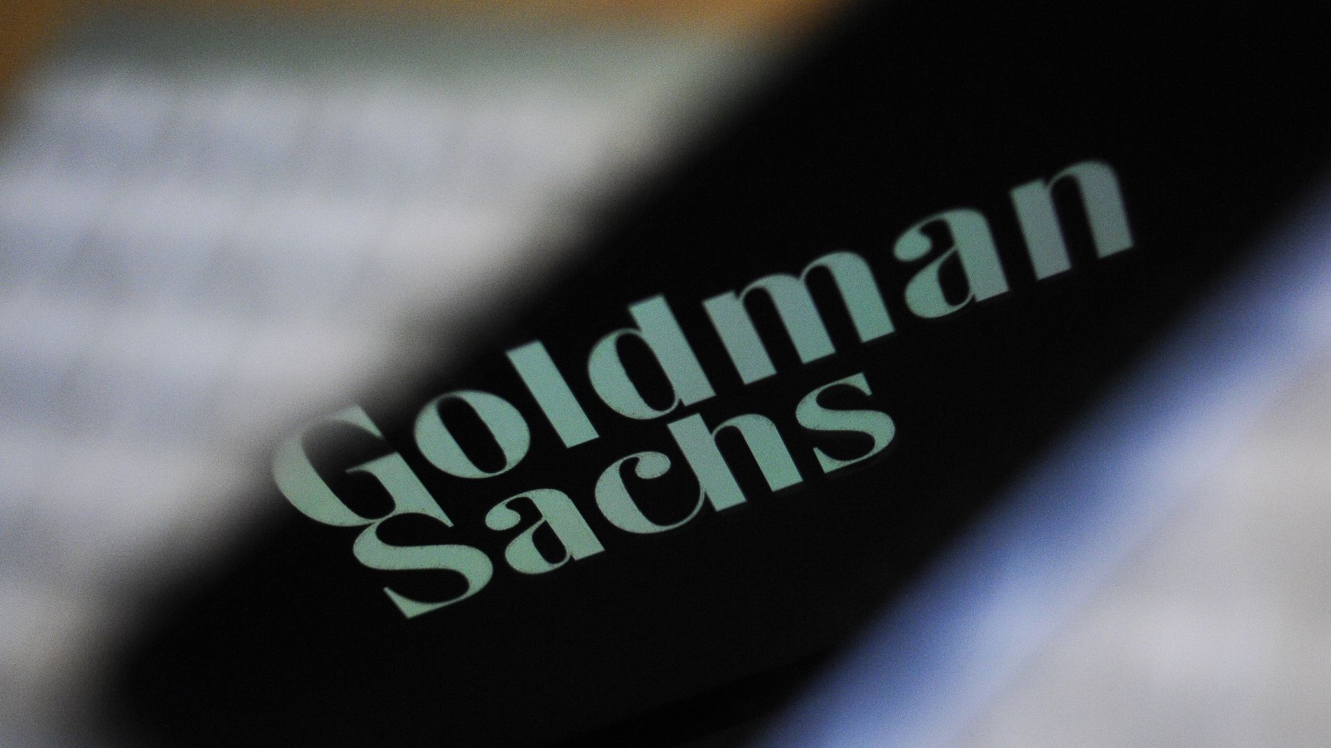 The Goldman Sachs bank logo is seen reflected on the screen of a mobile phone.