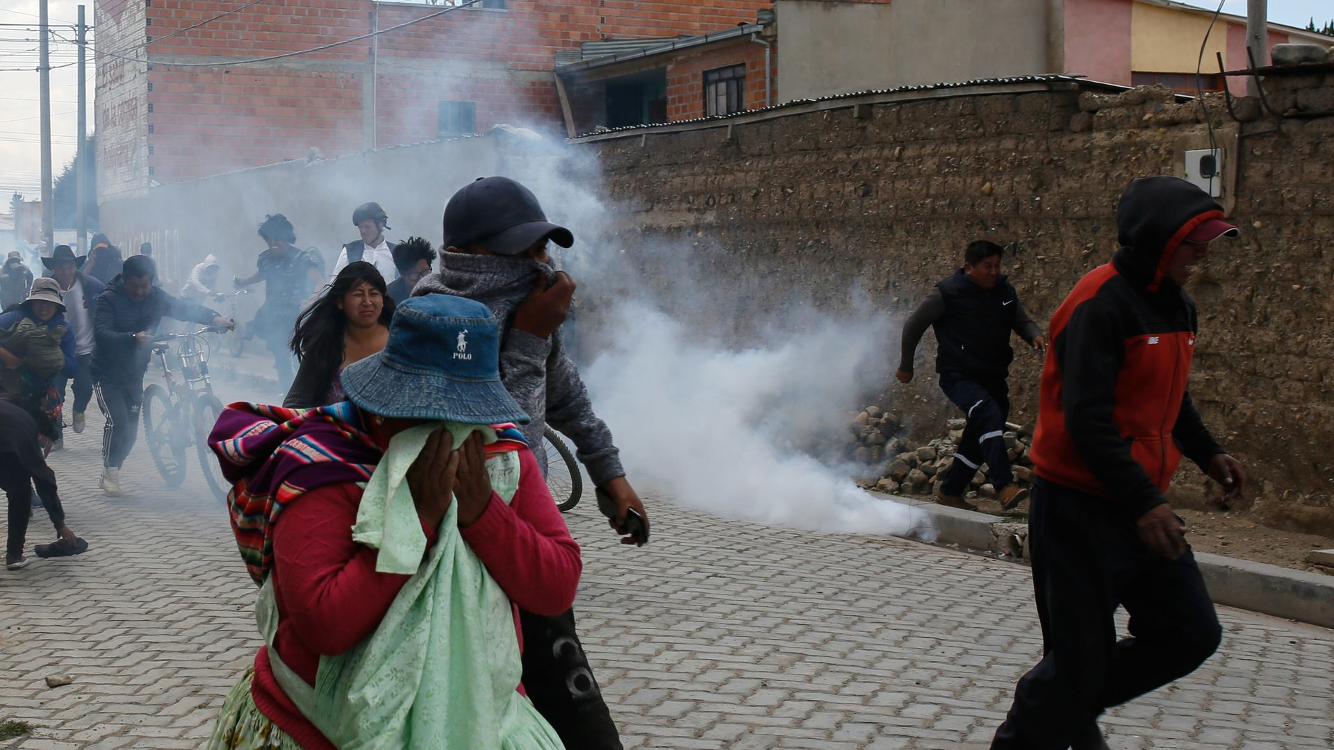 Supporters of Evo Morales run from tear gas as clashing with police during protests on November 19