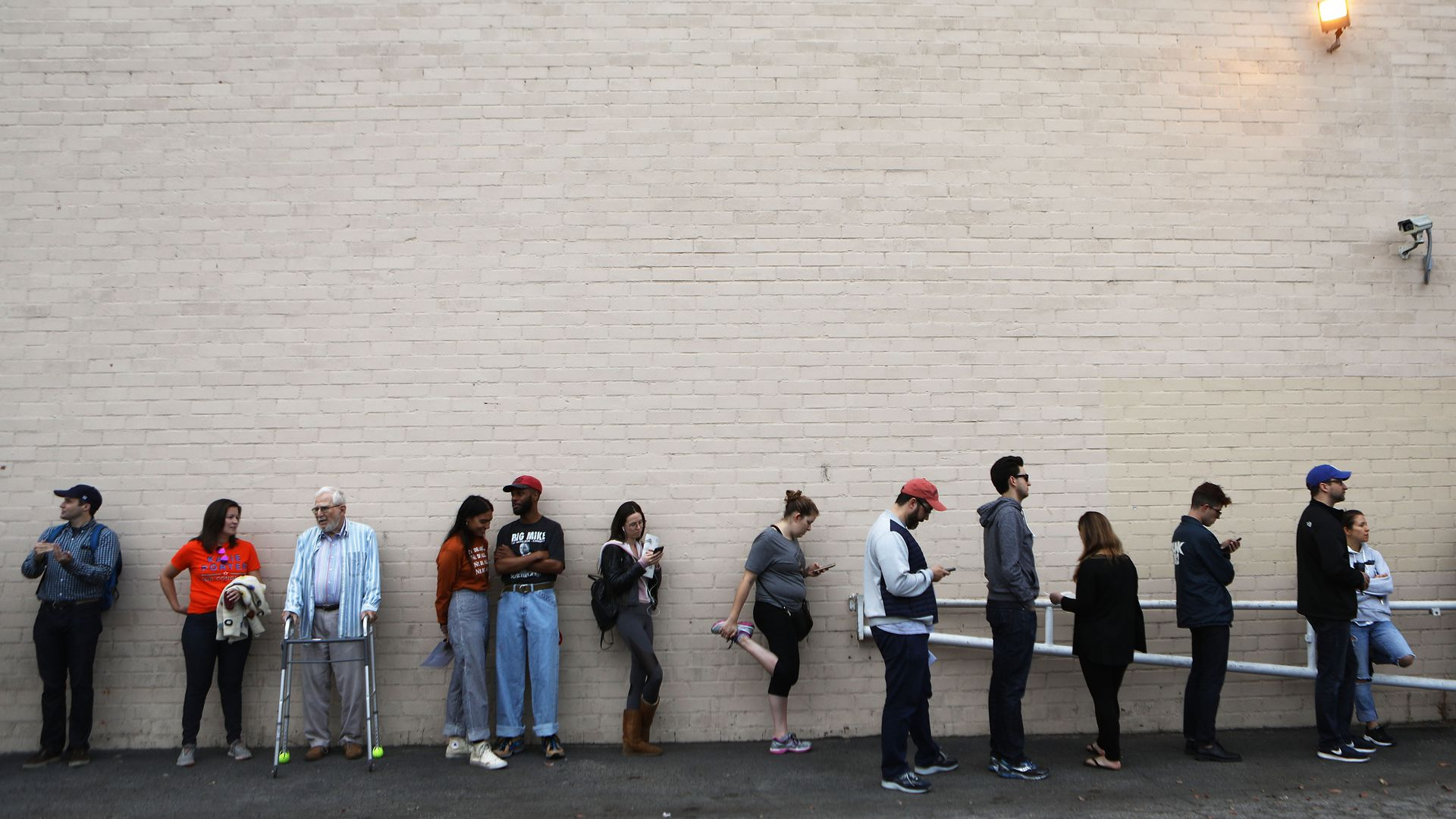 People stand in line to vote at a polling site. There is an old man with a walker and one woman stretching her legs.