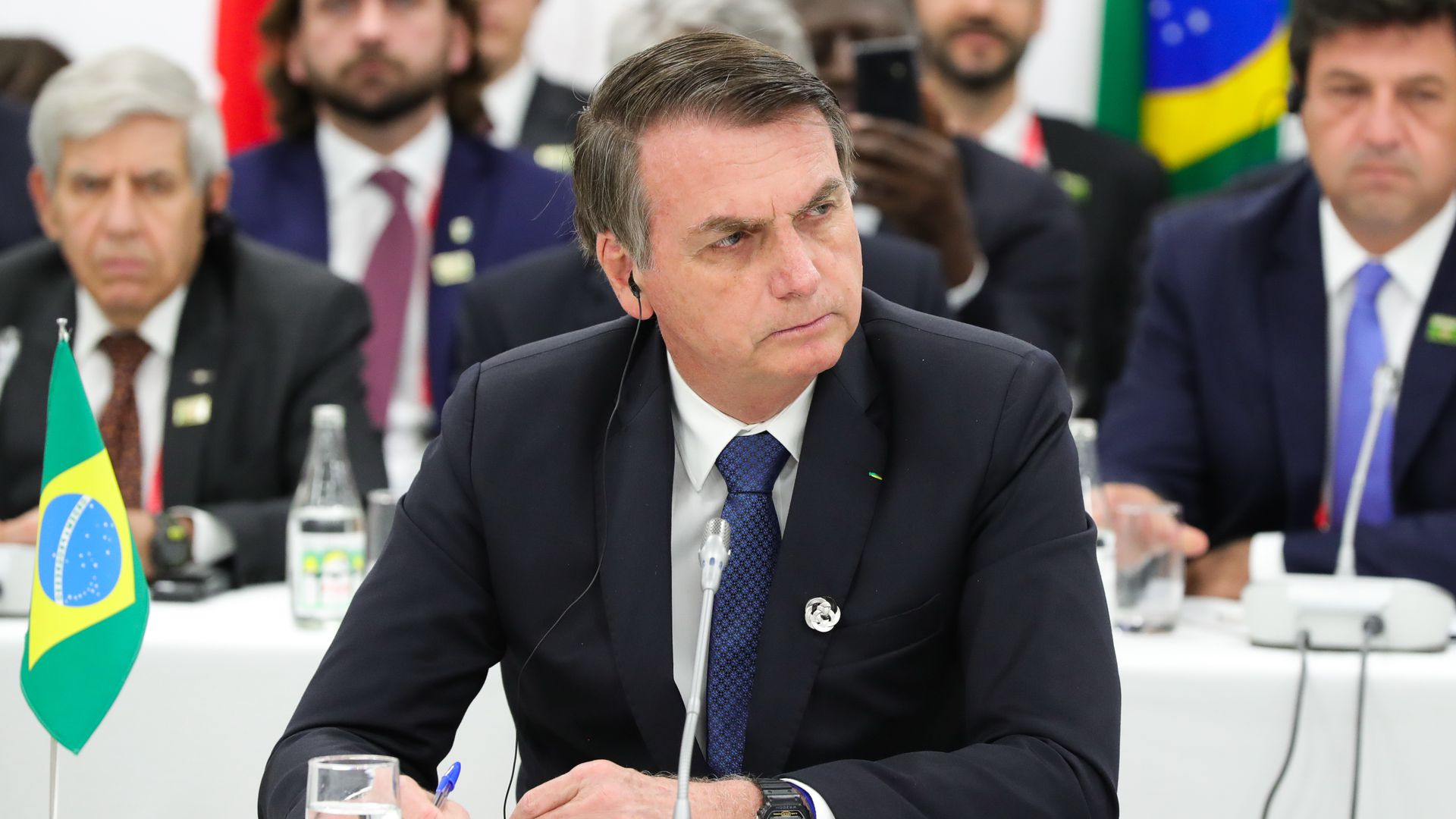 Bolsonaro sitting down and looking to the side.