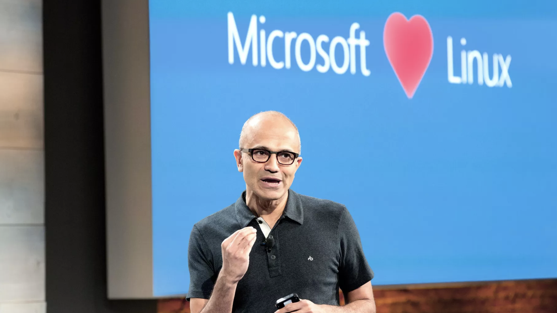 "Microsoft CEO Satya Nadella in front of a sign reading ""Microsoft Loves Linux"""