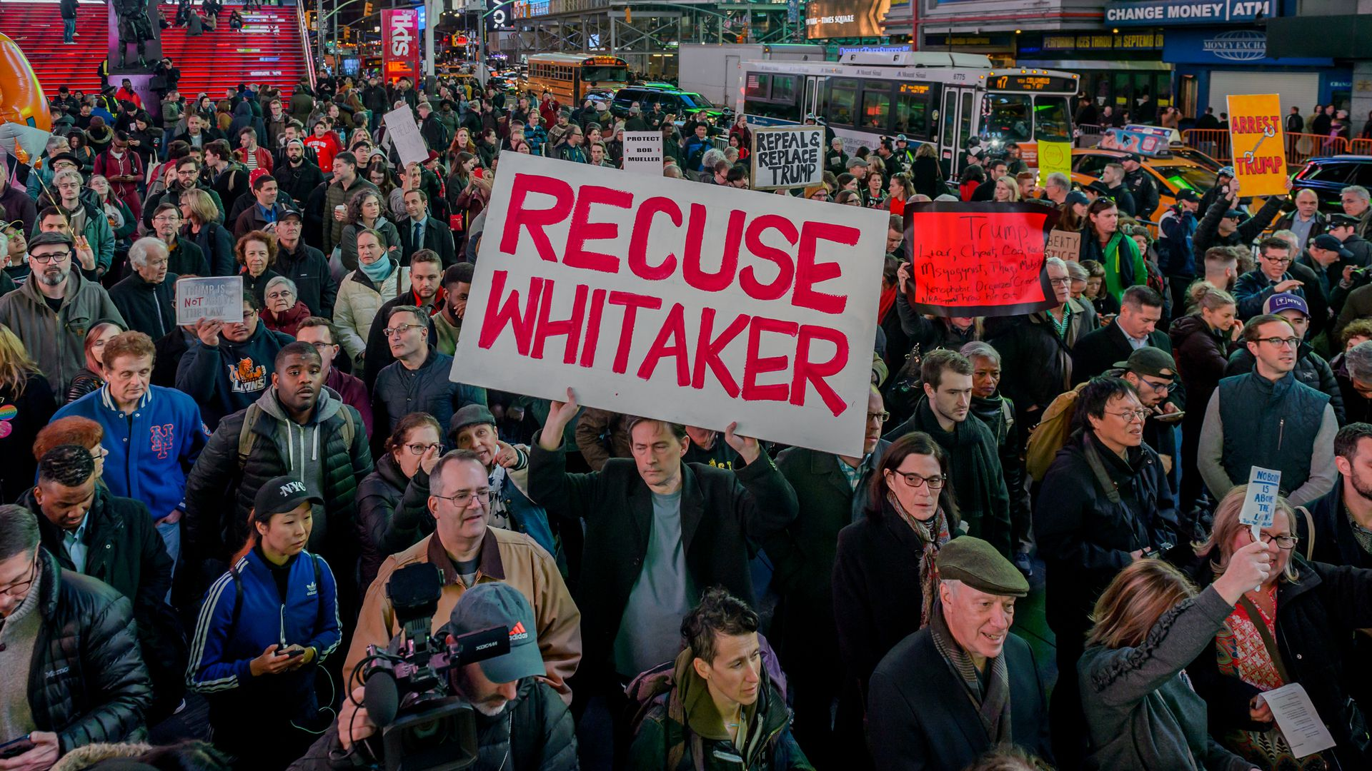 "A crowd of people protesting with one big sign that reads, ""Recuse Whitaker"" in reference to the current acting attorney general matthew whitaker."