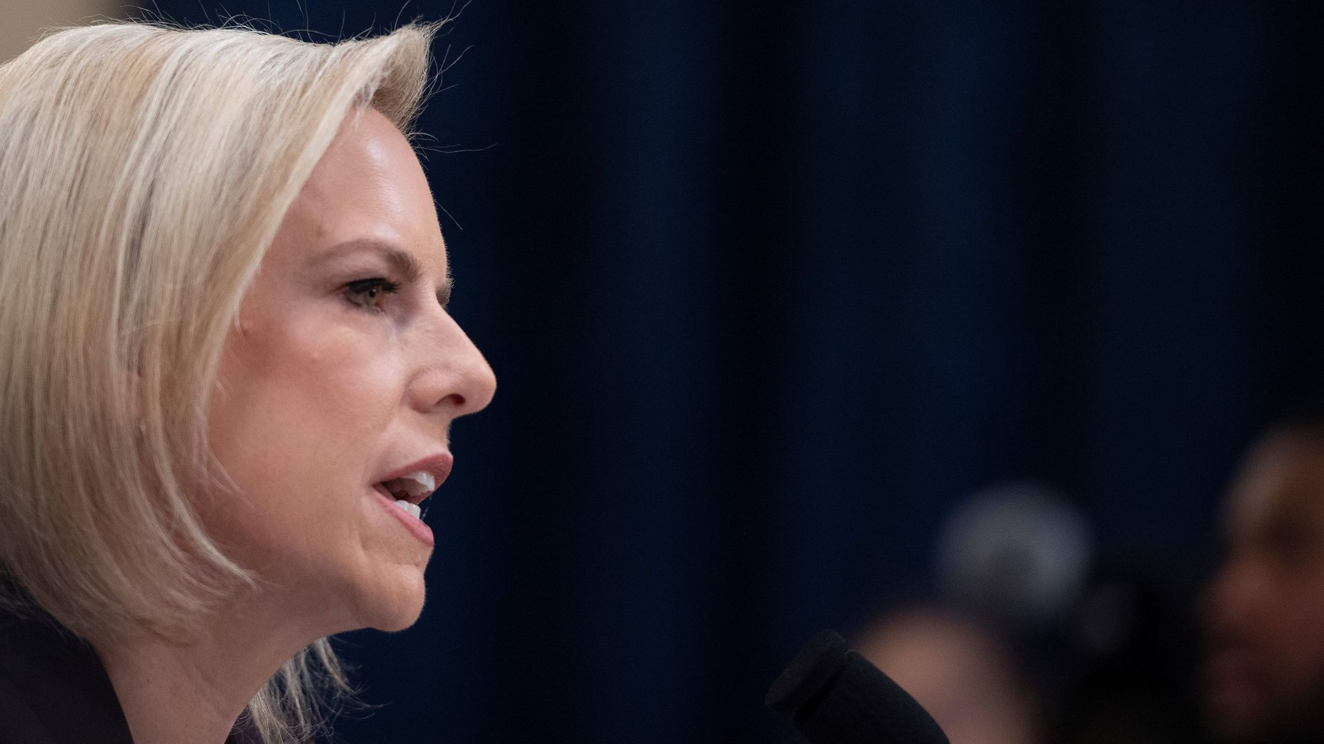 DHS Secretary Kirstjen Nielsen's profile as she speaks into a microphone with a serious face.