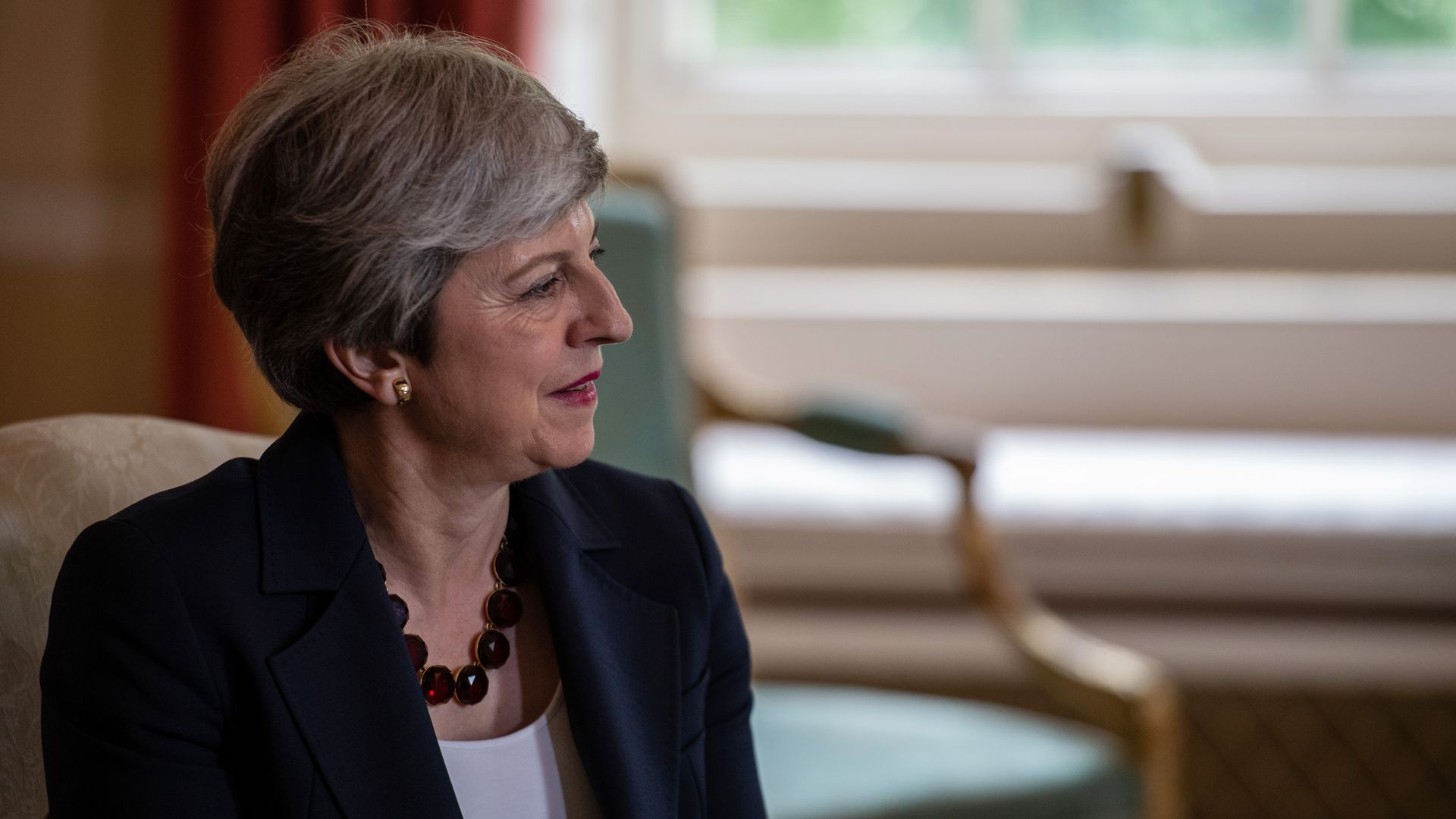 In this image, Theresa May sits and listens to someone speaking to her right.