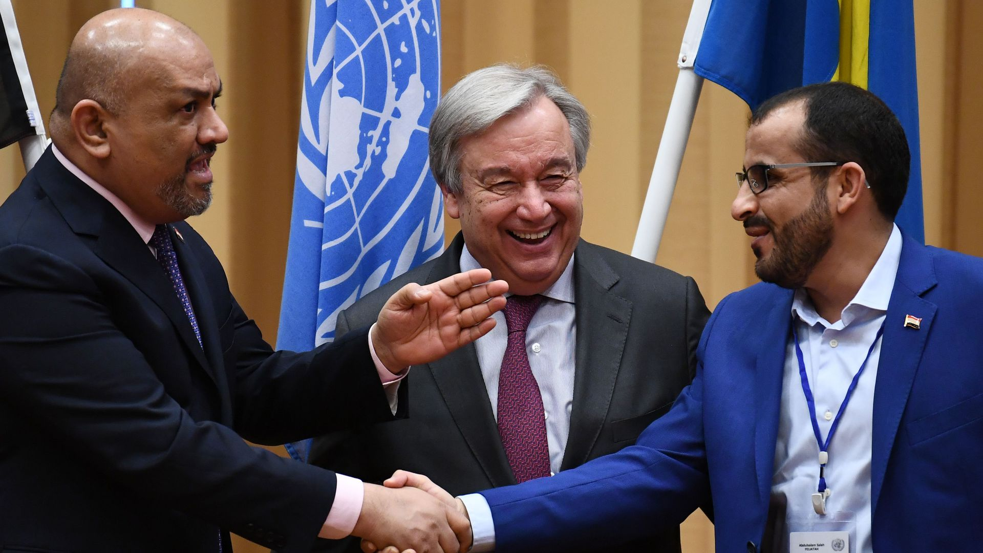 Yemen's foreign minister Khaled al-Yamani (L) and rebel negotiator Mohammed Abdelsalam (R) shake hands under the eyes of United Nations Secretary General Antonio Guterres during peace consultations