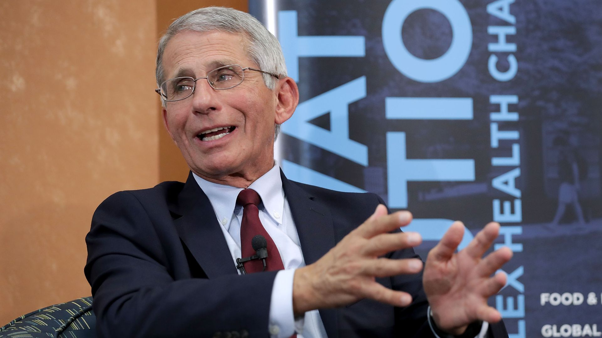 NIAID chief Anthony Fauci speaking at another panel, sitting down and gesticulating with his hands
