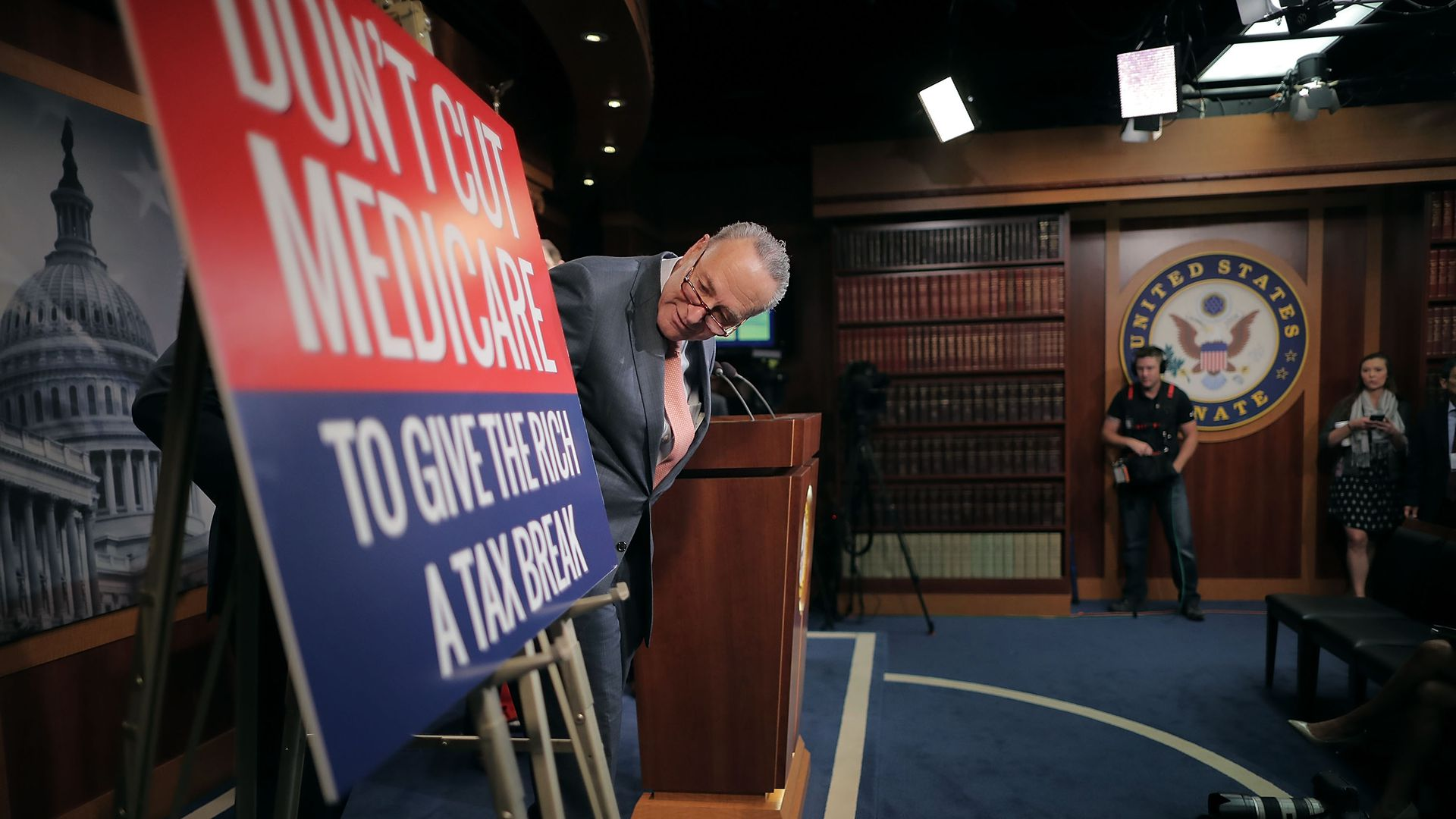 Chuck Schumer leaning over to look at a sign about health care and taxes