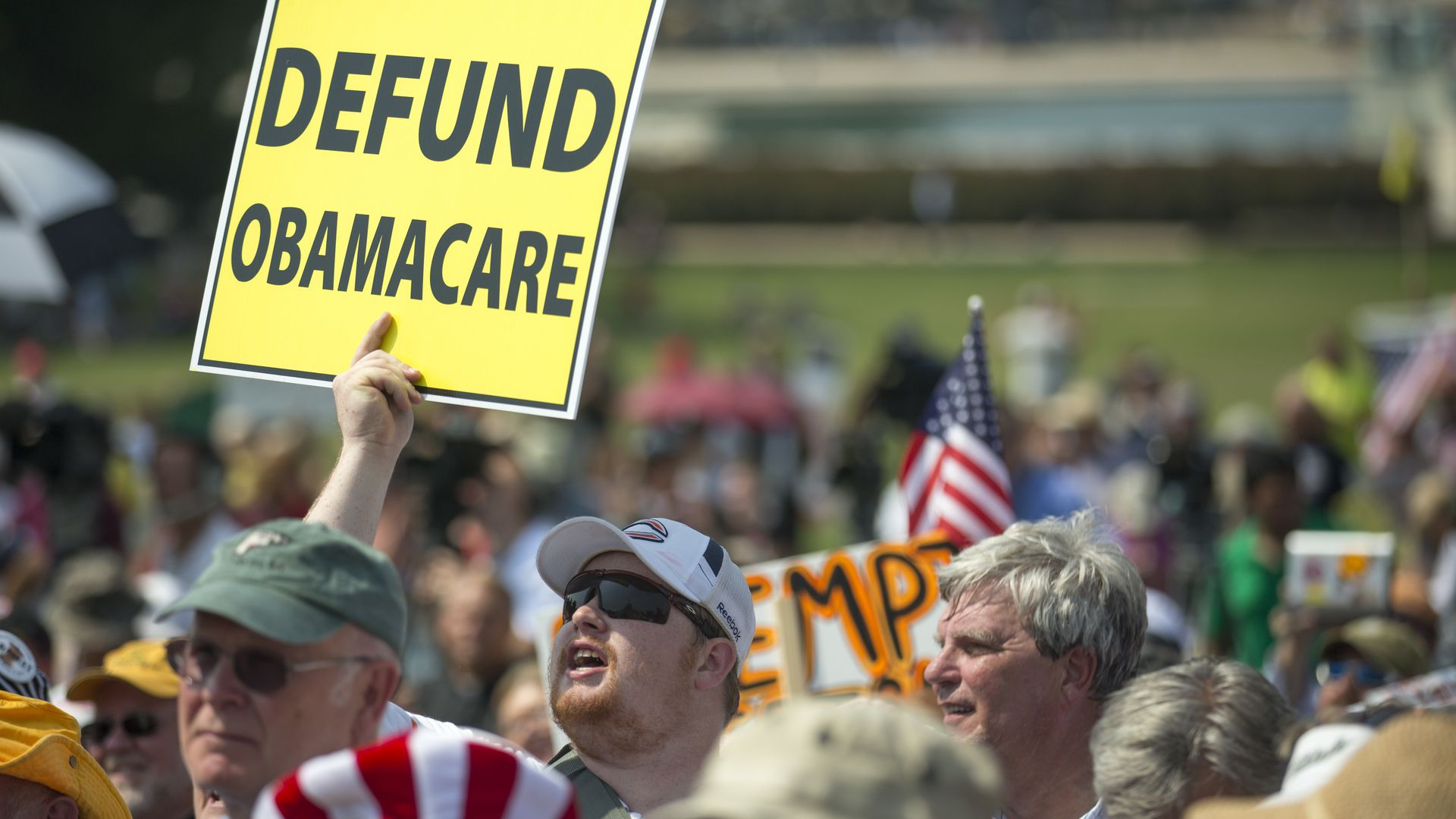 "A crowd of people, with a man holding a sign that says ""Defund Obamacare"""