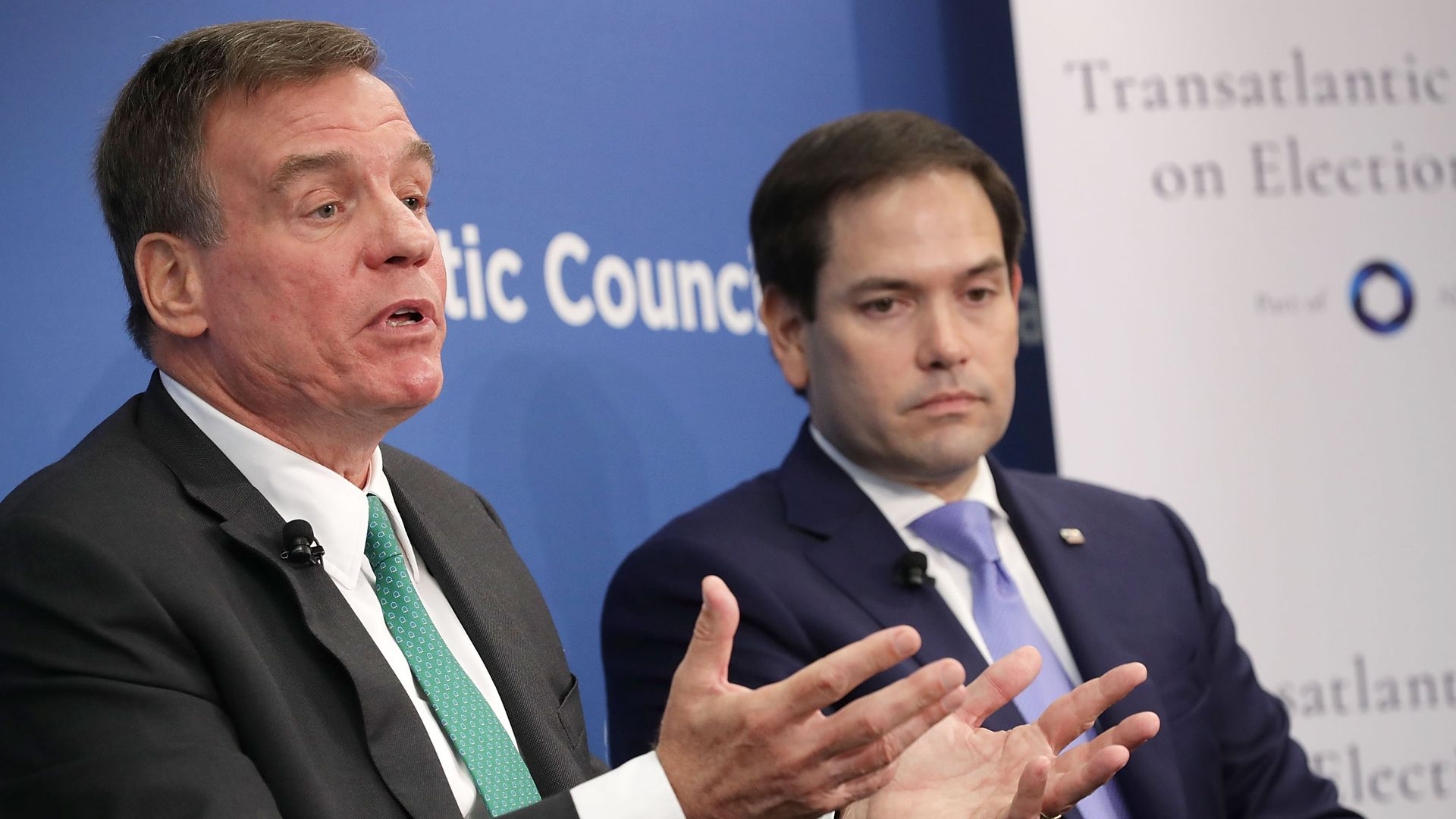 Mark Warner gestures while talking and Marco Rubio looks on sternly