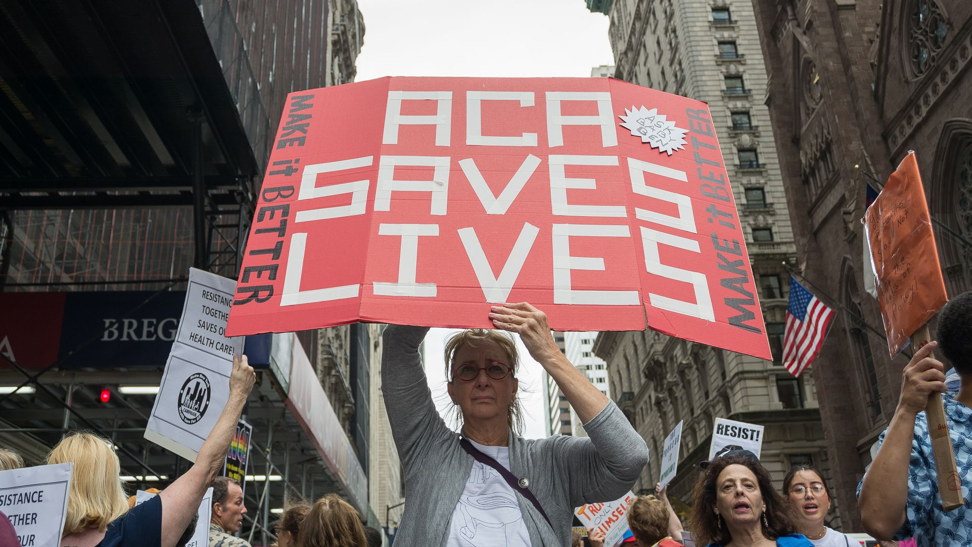 "A demonstrator holds a sign that reads, ""ACA Saves Lives"""