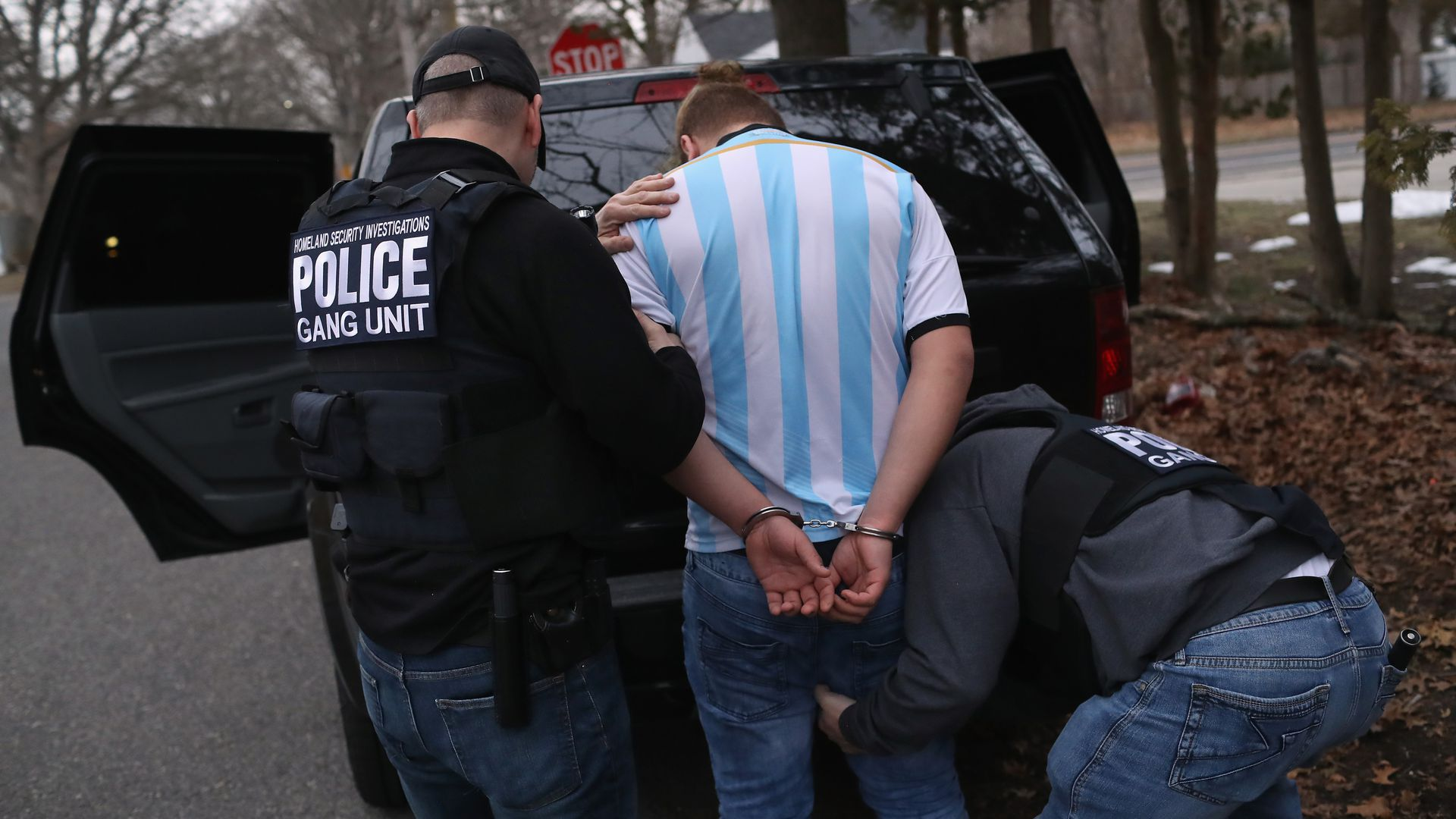 Two police officers frisking a suspected MS-13 gang member who is wearing a blue and white striped shirt and is in handcuffs