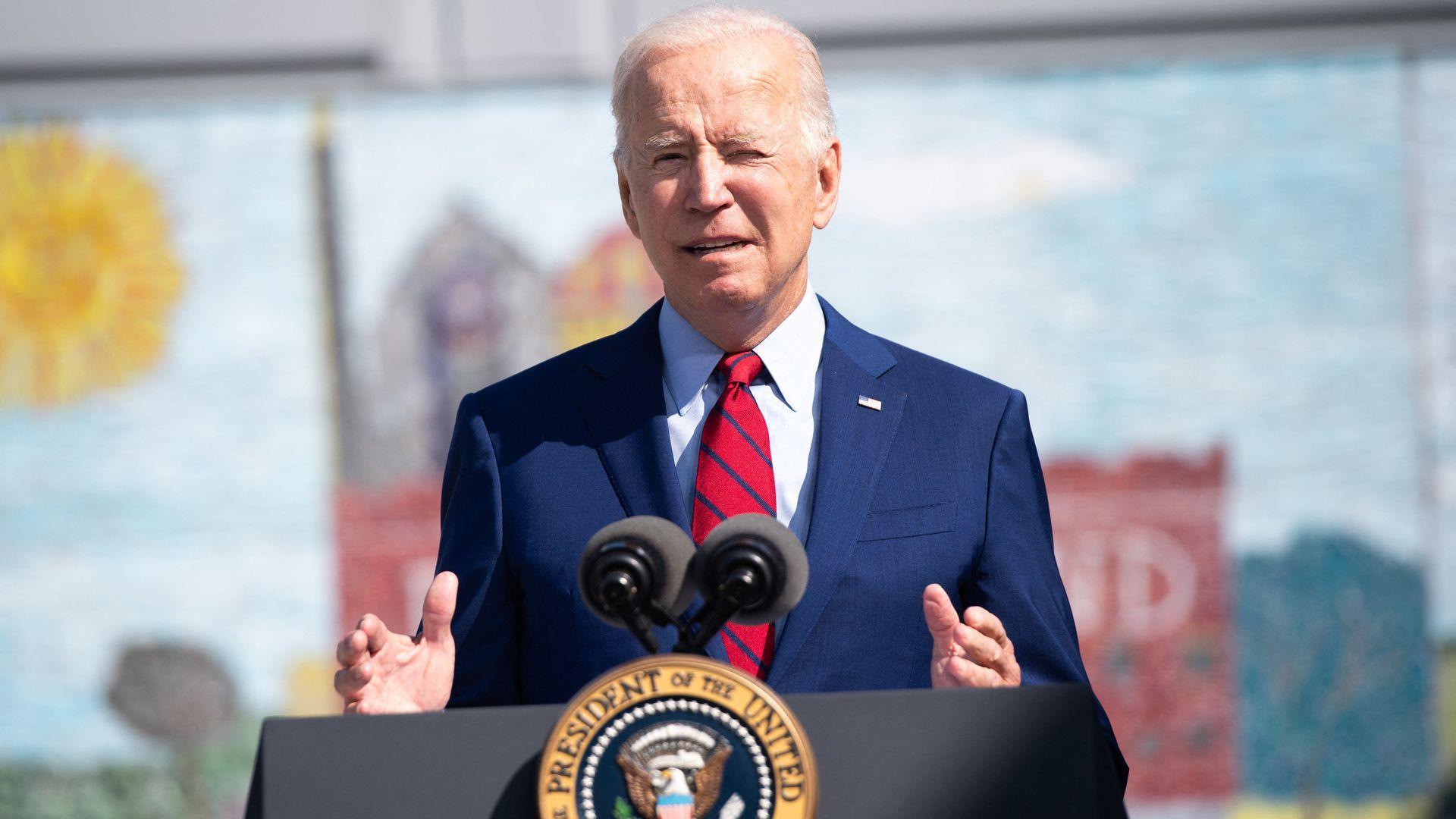 President Joe Biden speaks at a podium outdoors.