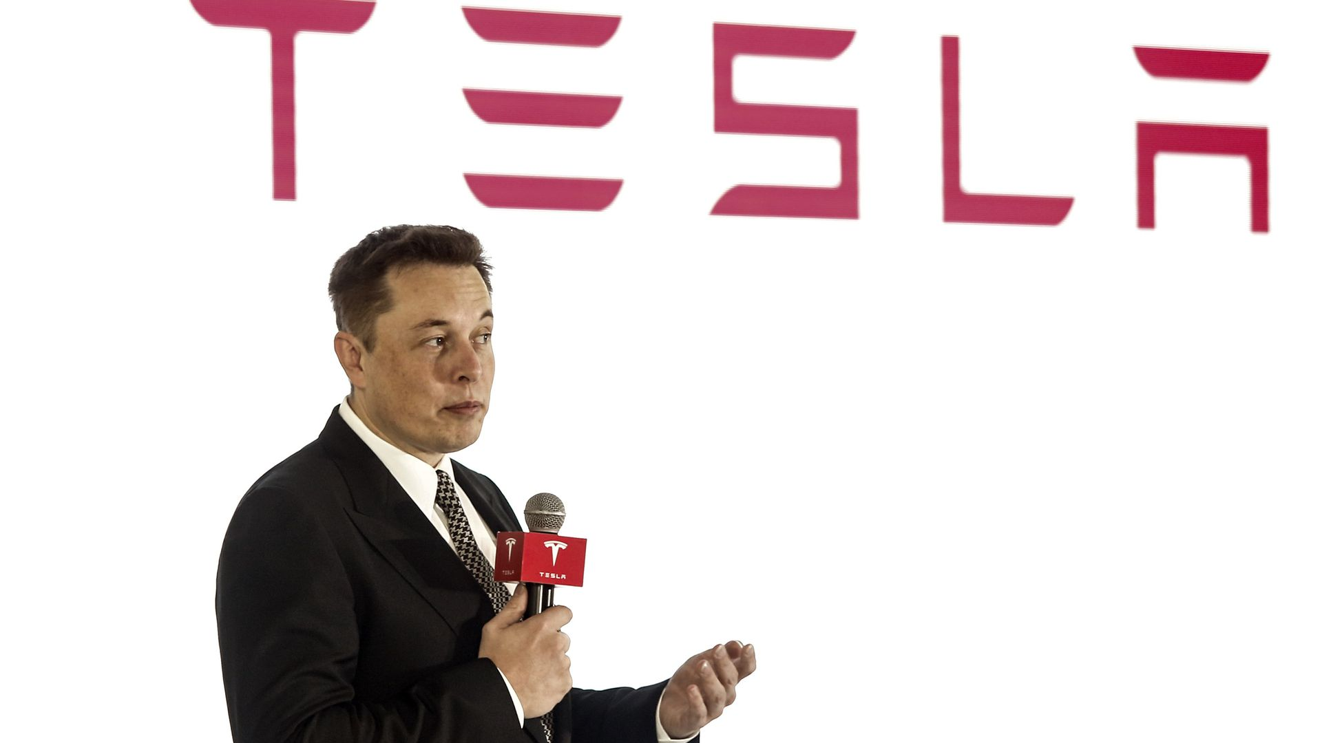 Elon mUsk in a suit on a stage with a microphone.